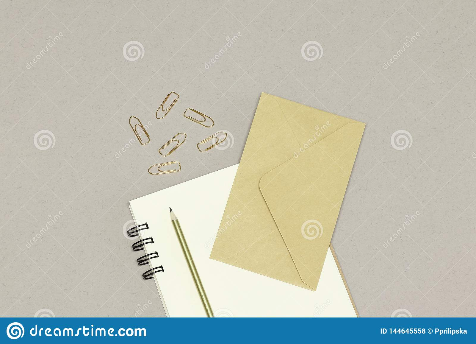 Конверт kraft, примечания, золотой карандаш & бумажные зажимы, на белой предпосылке