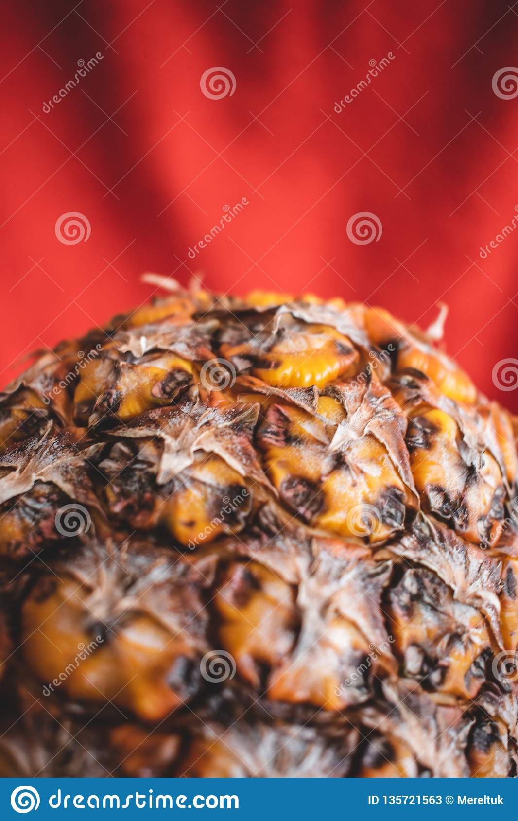 Конец вверх ананаса в красной предпосылке
