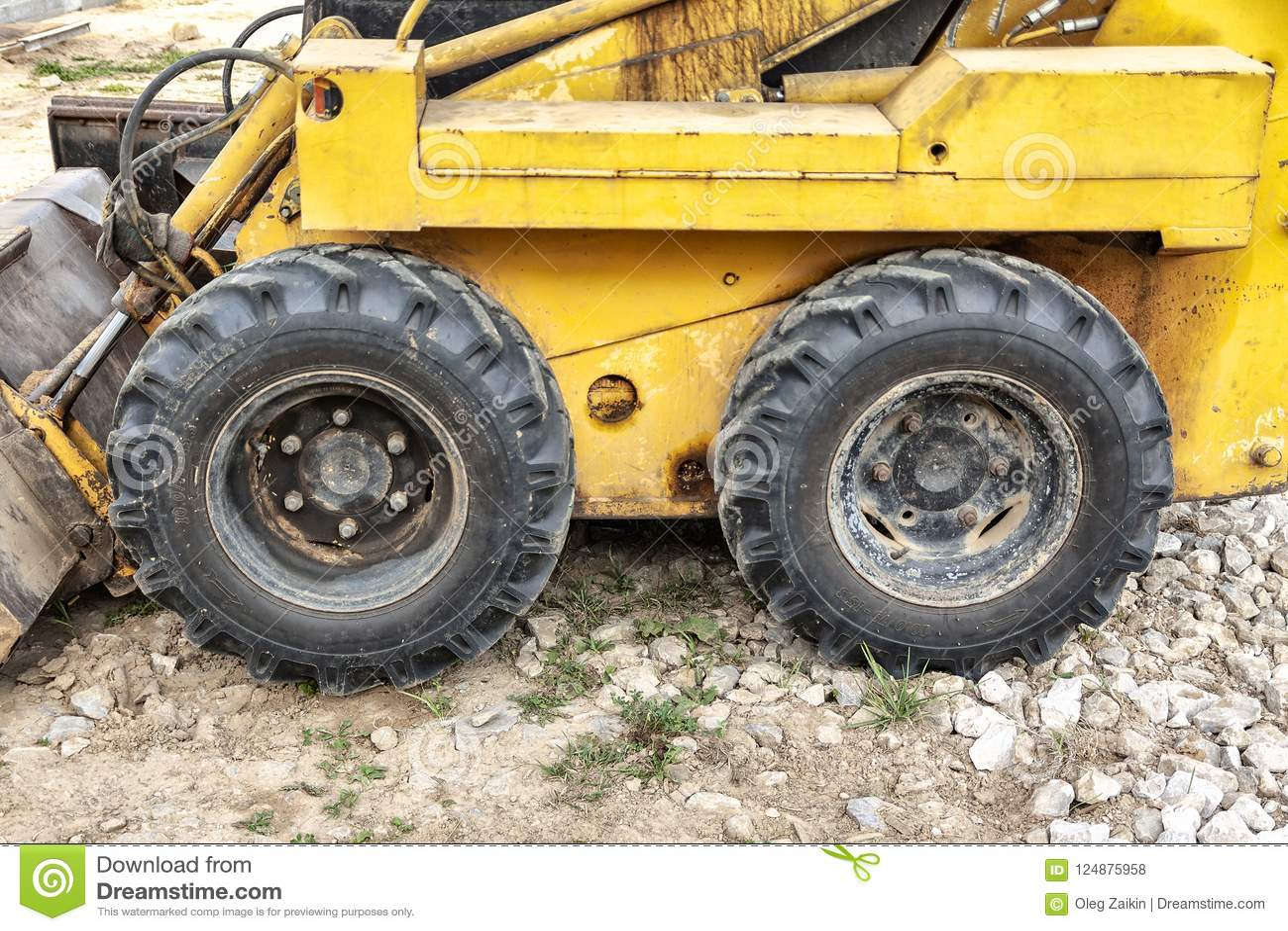 Конец-вверх желтого мини колеса экскаватора на строительной площадке