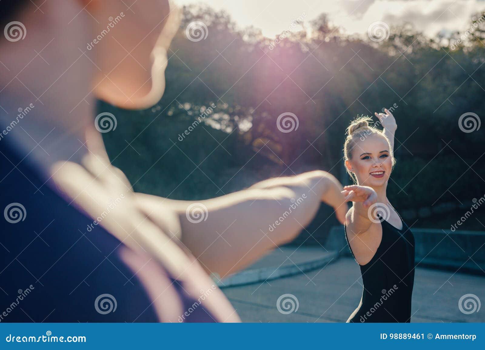 Конец вверх женских артистов балета практикуя дуэт танцует