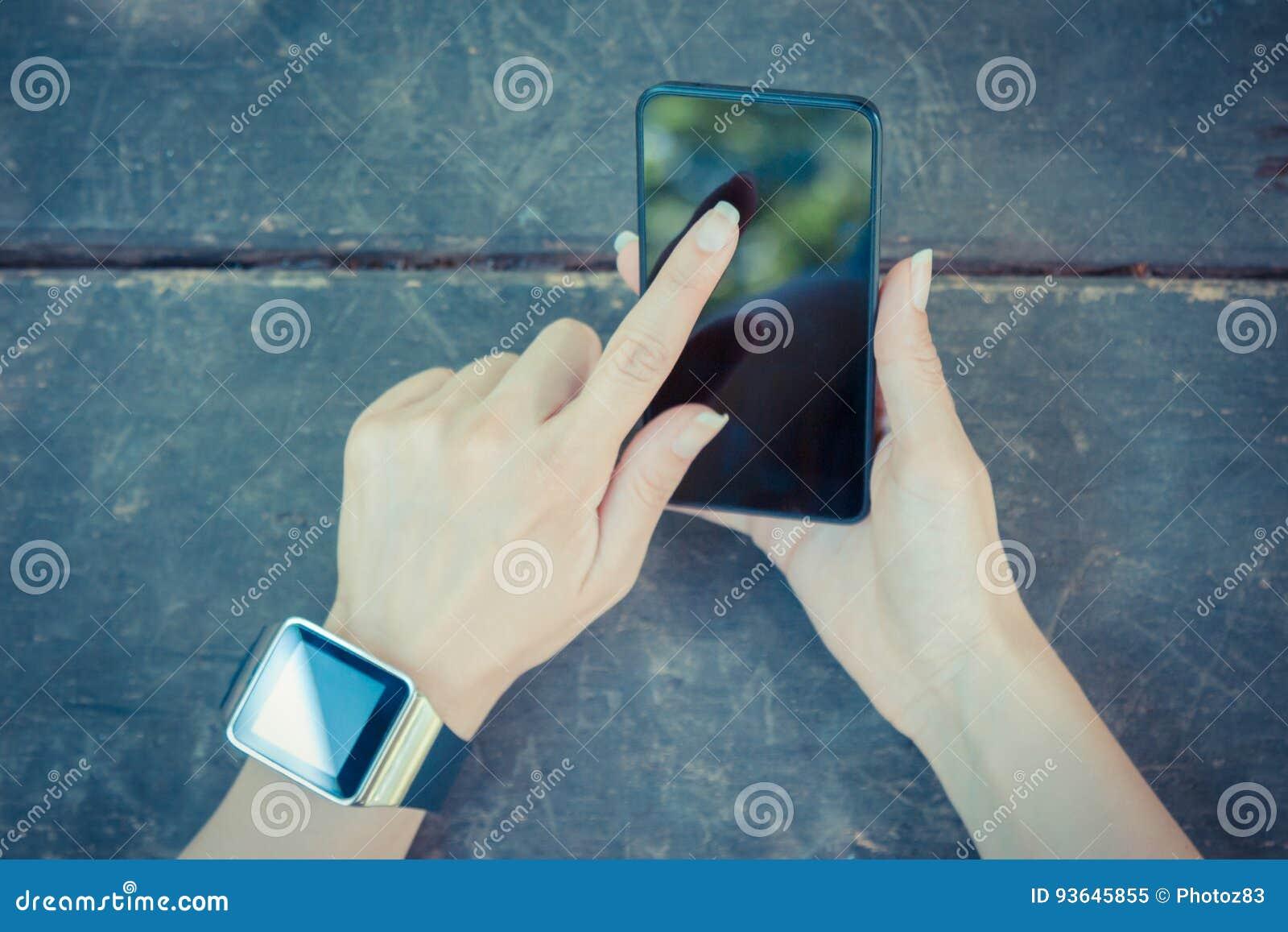 Конец вверх женской руки держа умный телефон и нося вахту