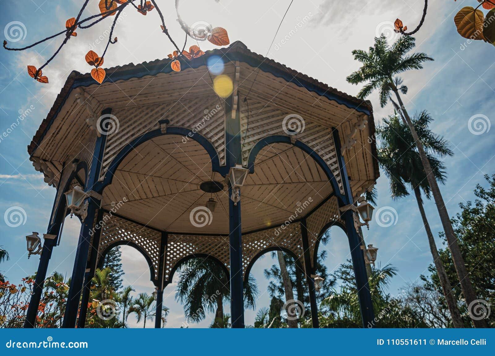 Конец-вверх красочного потолка газебо в середине сада вполне деревьев, в ярком солнечном дне на São Манюэле