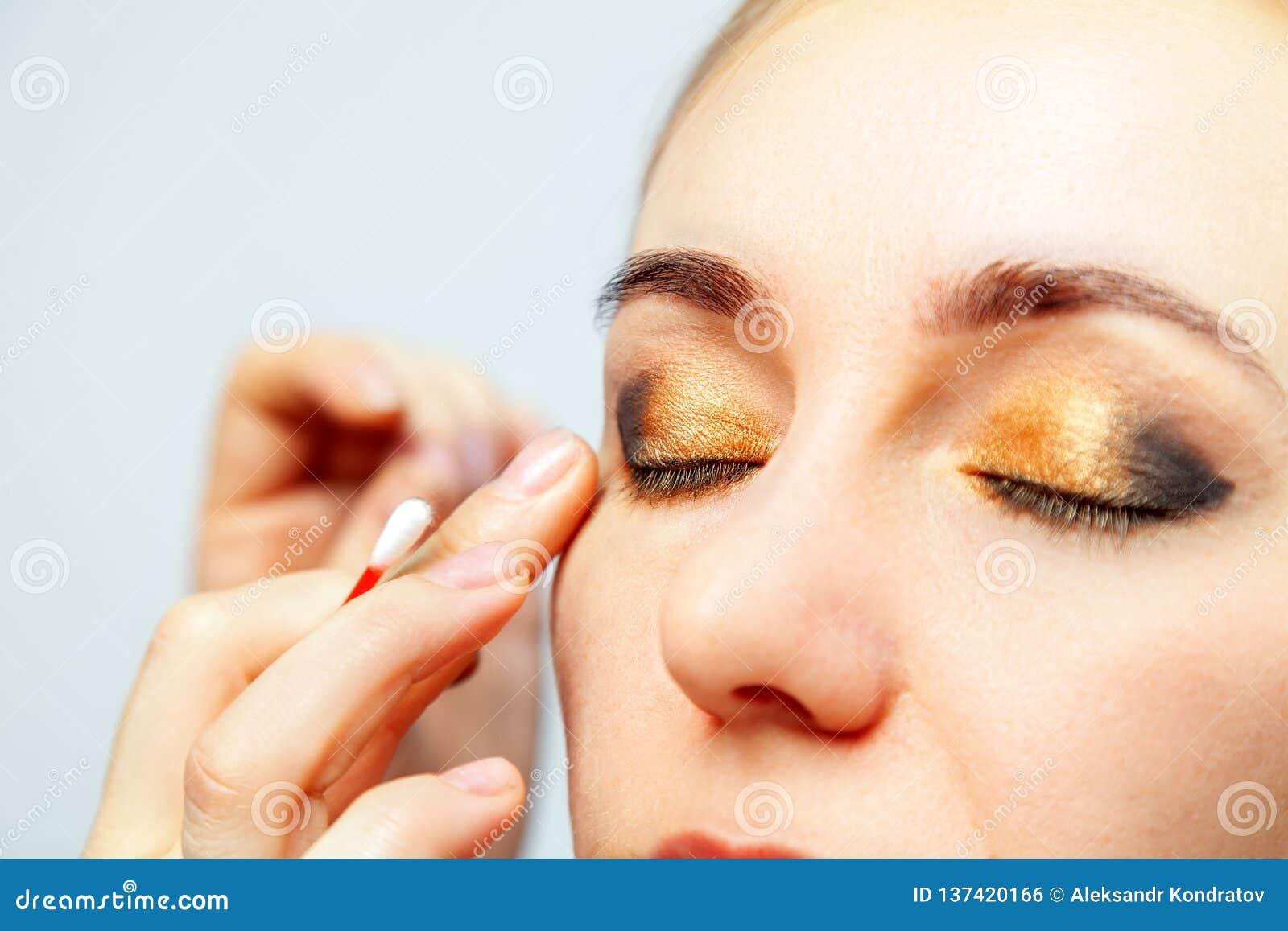 Конец-вверх макияжа глаз модели с цвета свет стороной, художник макияжа держит пробирку хлопка в его руках и