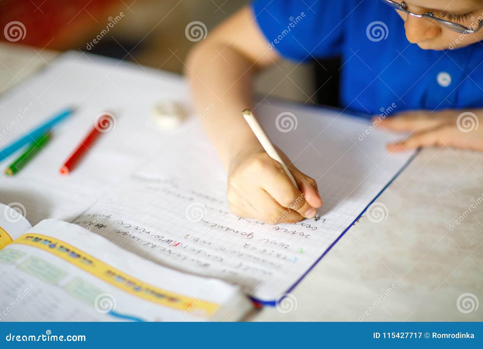 Конец-вверх мальчика маленького ребенка при стекла дома делая домашнюю работу, писать письма с красочными ручками