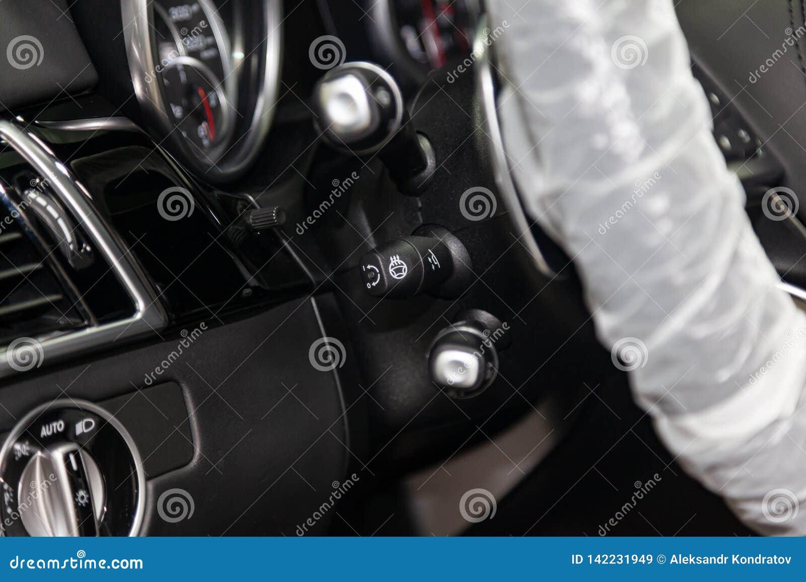 Конец-вверх на части интерьера современного роскошного автомобиля с целью нагретой кнопки руля с черной деревянной отделкой
