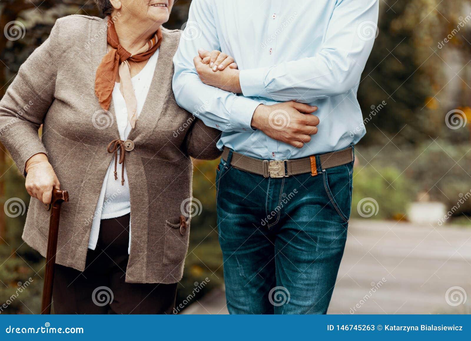 Конец-вверх на человеке поддерживая старшую женщину с идя ручкой