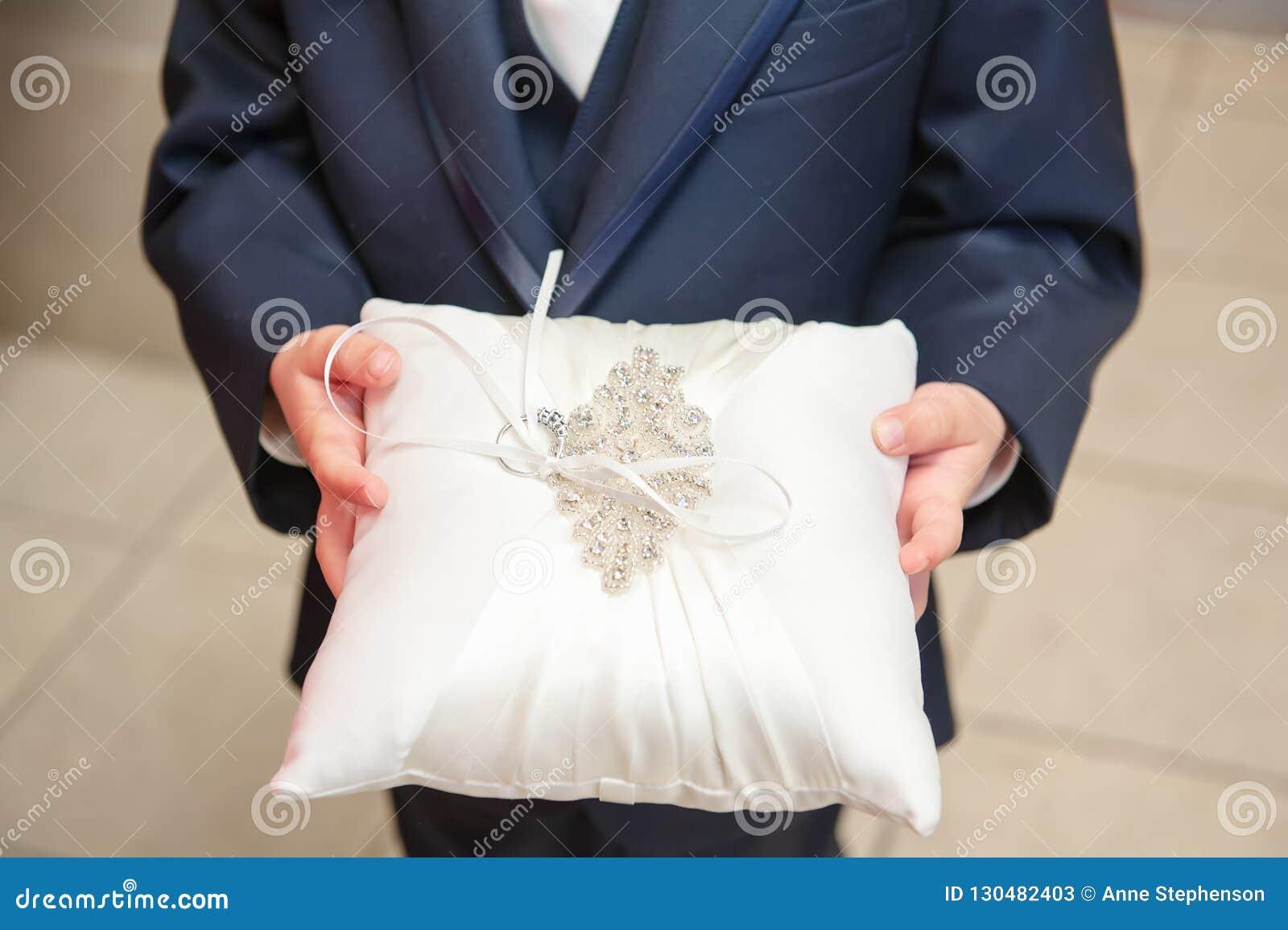 Конец вверх по взгляду подателя кольца держа bridal подушку свадьбы украшенный с sequins и кольцом невесты