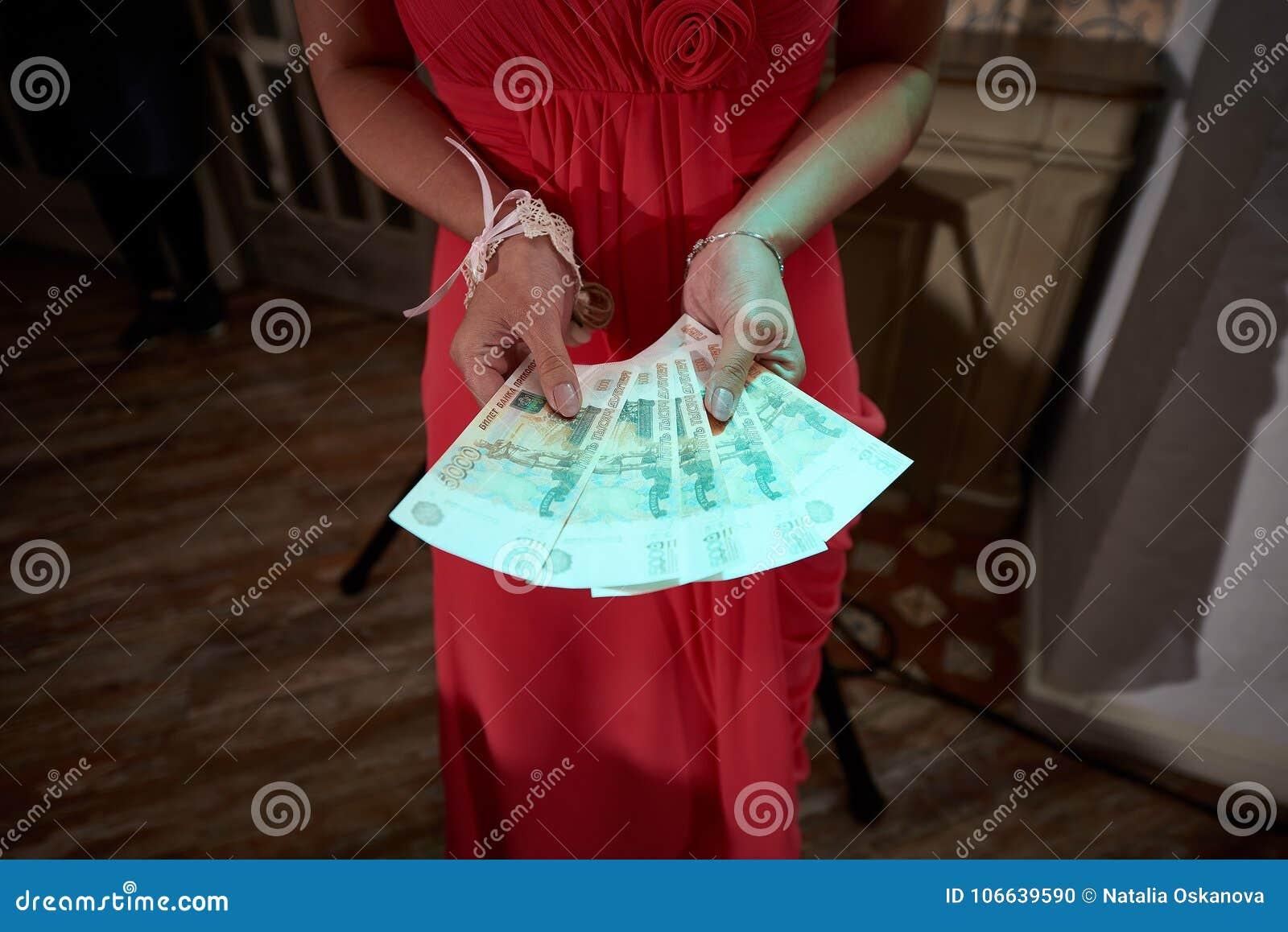 Конец вверх по женщине в красном платье держит деньги