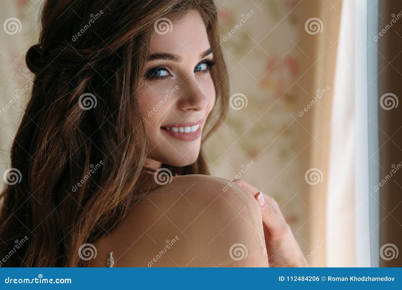 Конец вверх по портрету красивой невесты с милым smite в белом платье свадьбы стоит в ее комнате в гостинице, утре