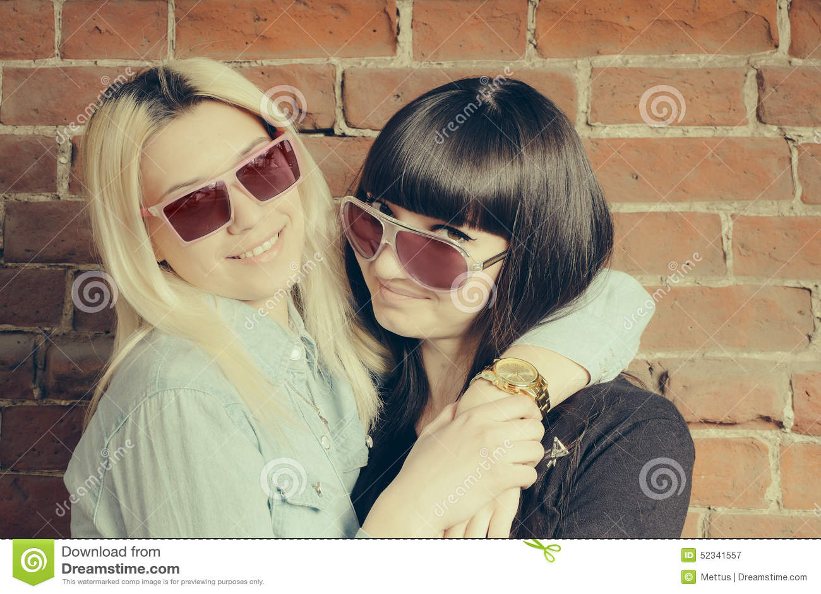 Конец вверх по портрету моды 2 объятий девушек и потех иметь совместно, нося стильные солнечные очки, самый лучший fiend наслажда