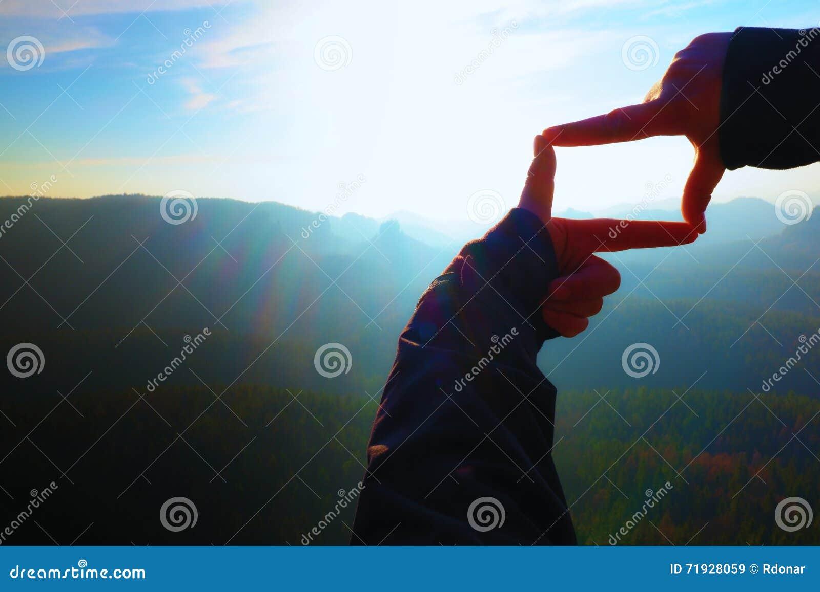Конец вверх по рукам делает рамку показывать Пик голубой туманной мембраны долины скалистый Солнечный рассвет весны