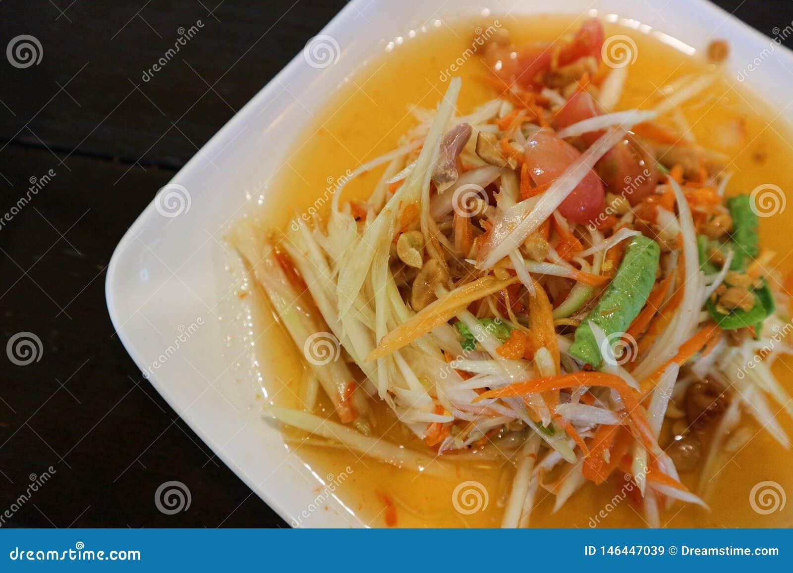 Конец вверх по салату тайской папапайи пряному или животик сома в белой плите и черной предпосылке