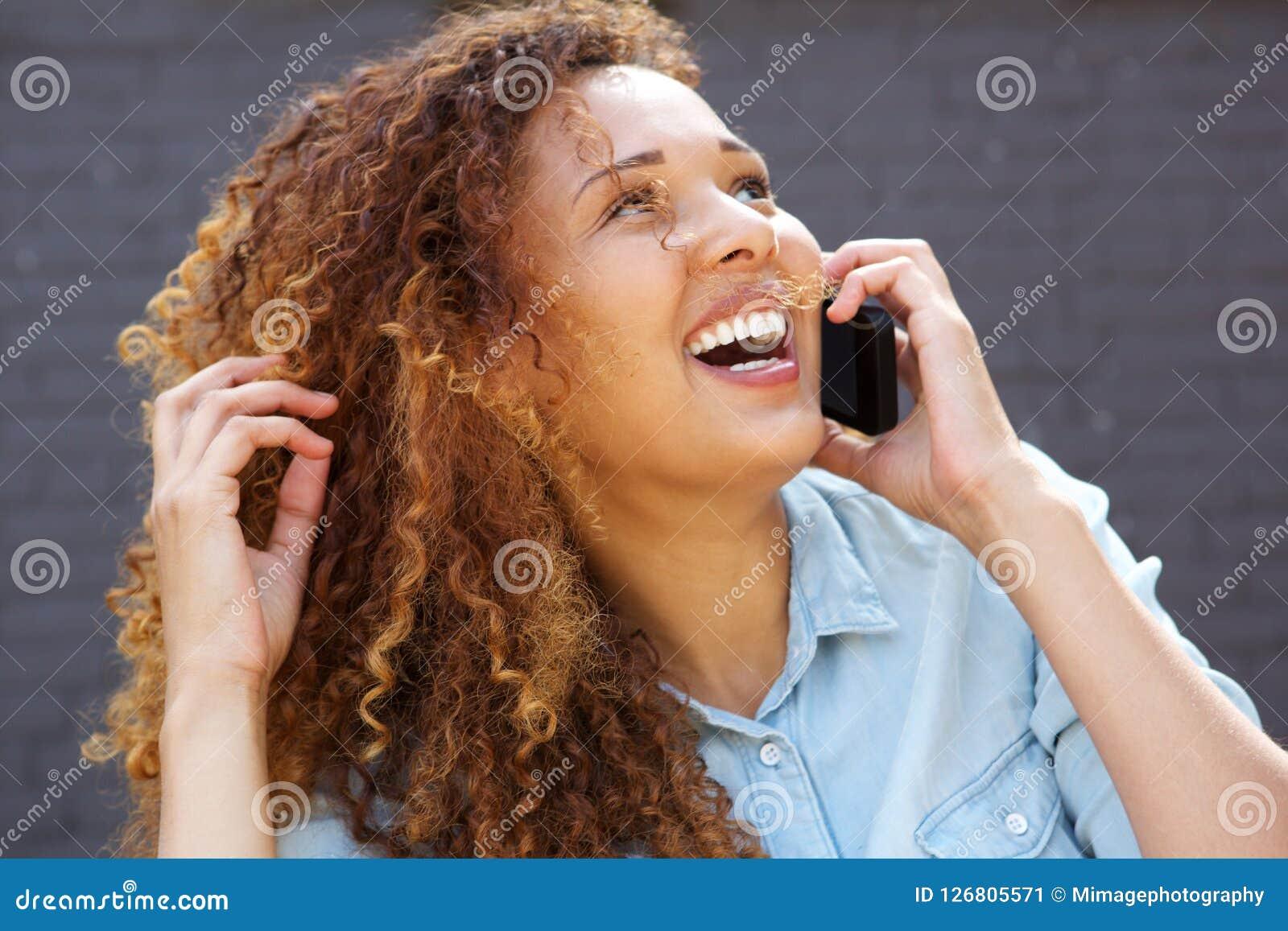 Конец вверх по счастливой молодой женщине смеясь и говоря на мобильном телефоне