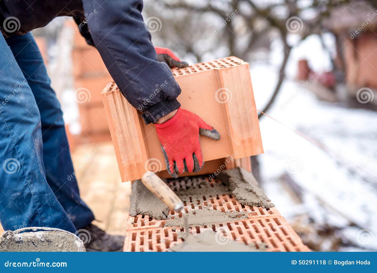 конец-вверх рабочий-строителя, каменщика строя новый дом с кирпичами