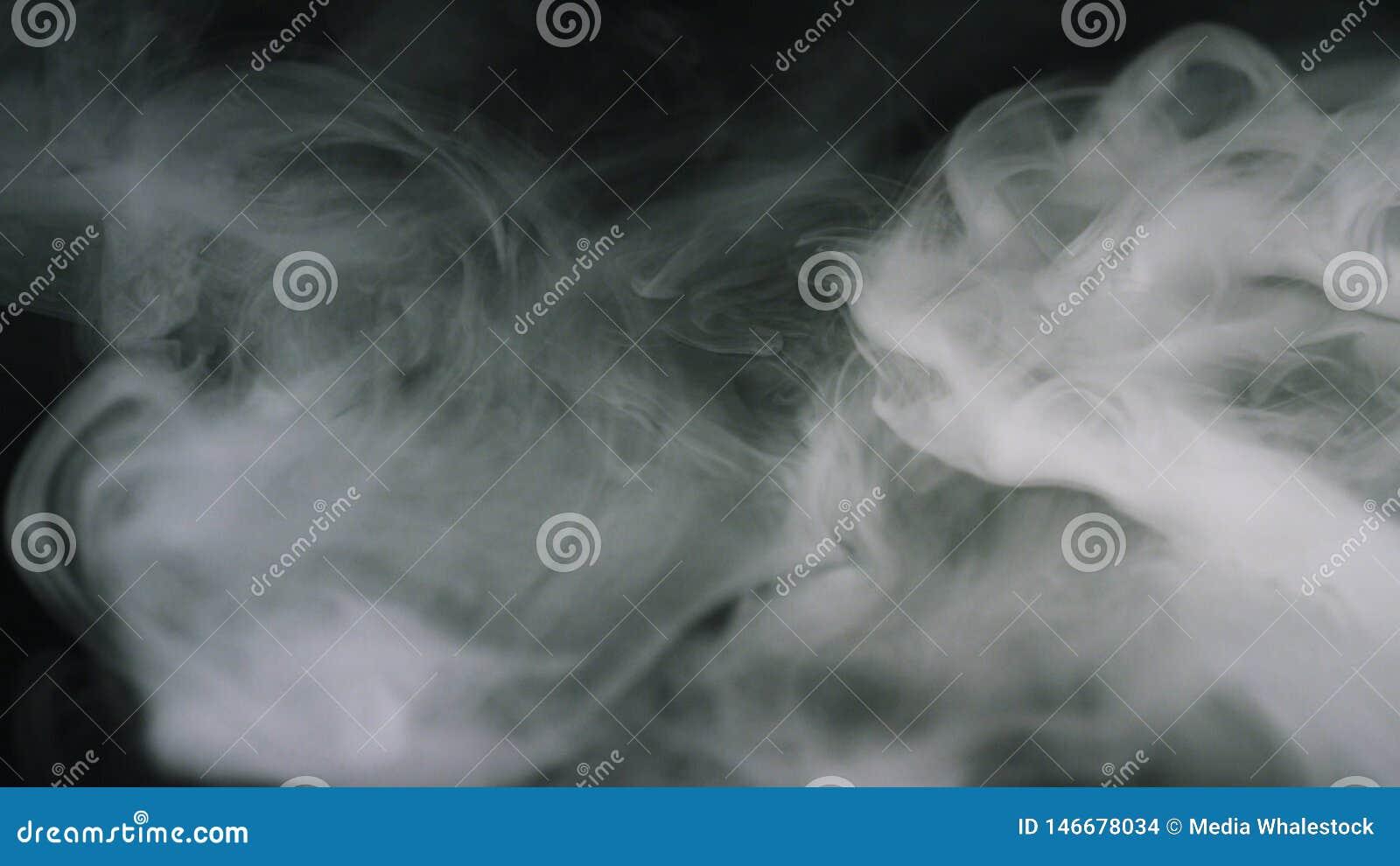 Конец-вверх слоек белого дыма плавая в темноту r на черном