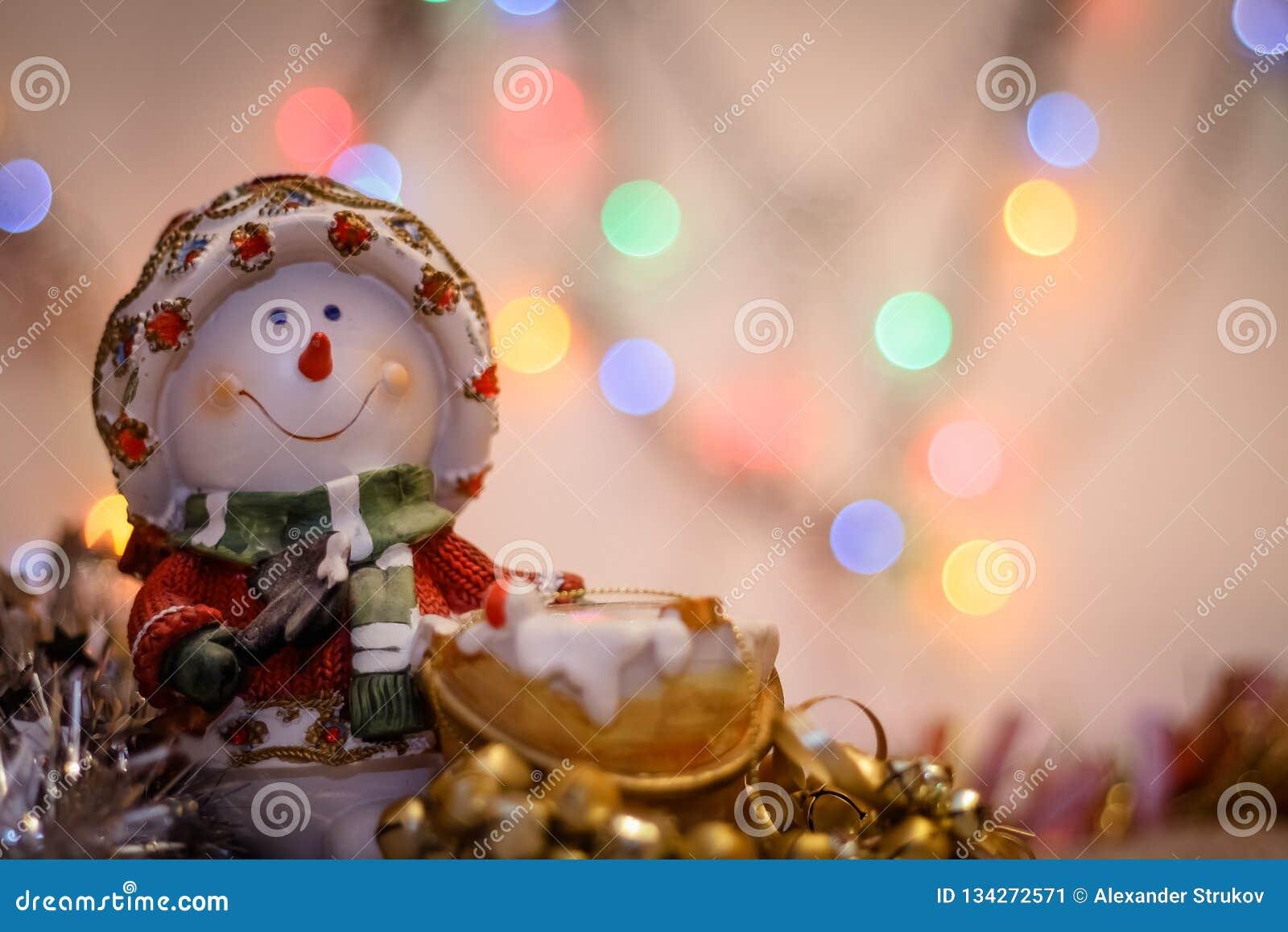 Конец-вверх снеговика на предпосылке расплывчатой покрашенной сусали светов и С Новым Годом!