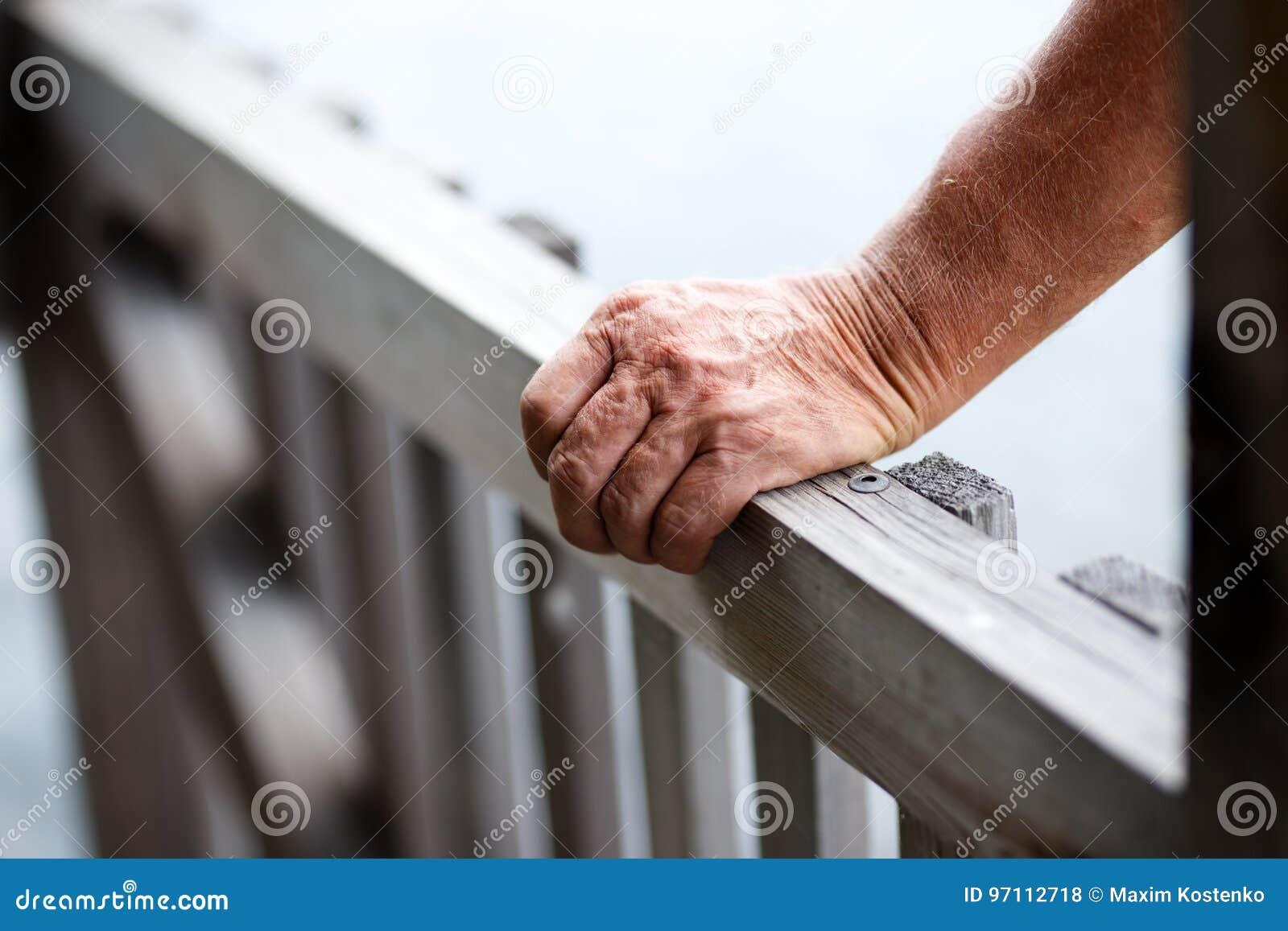 Конец-вверх старика стоя около деревянной загородки пока кладущ руку на прокладывать рельсы
