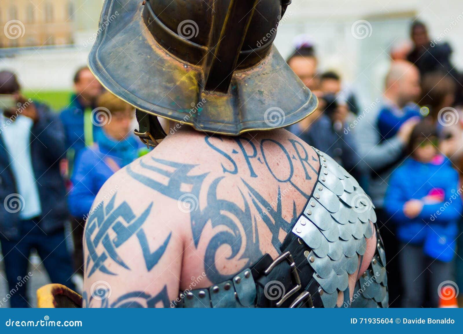 Конец вверх татуировки spqr на человеке одетом как римский солдат во время марша в Риме