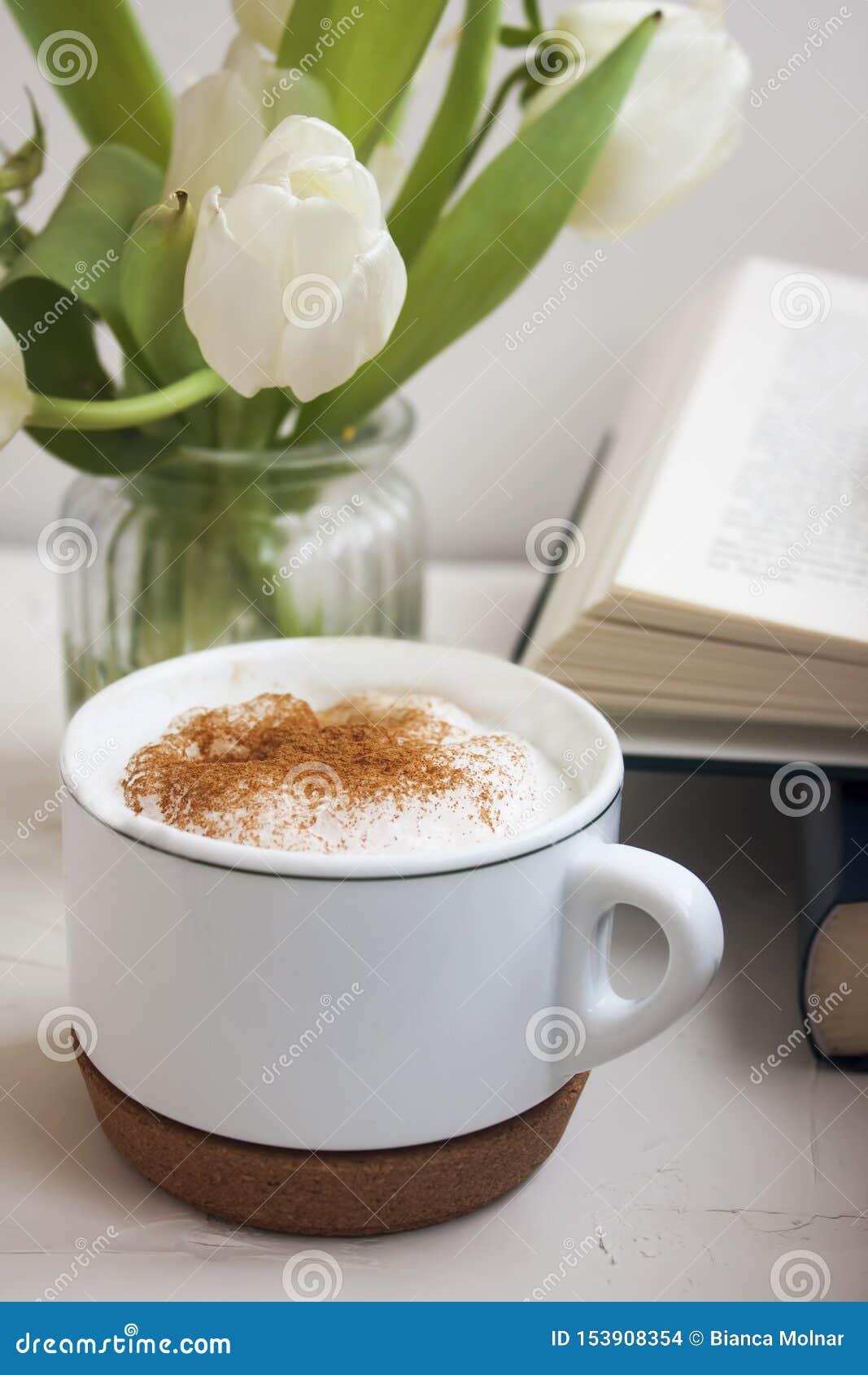 Конец-вверх теплой чашки кофе взбрызнутый с циннамоном