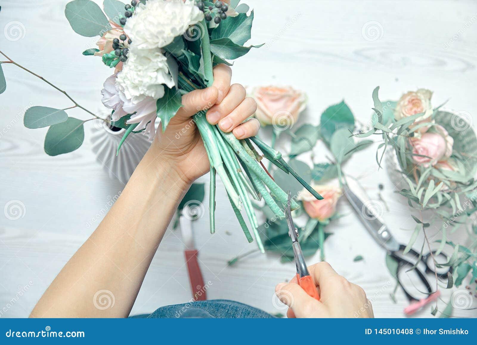 Конец взгляда сверху вверх по женскому положению цветков отрезков на счетчике Аранжировать различные цветки в современном свежем