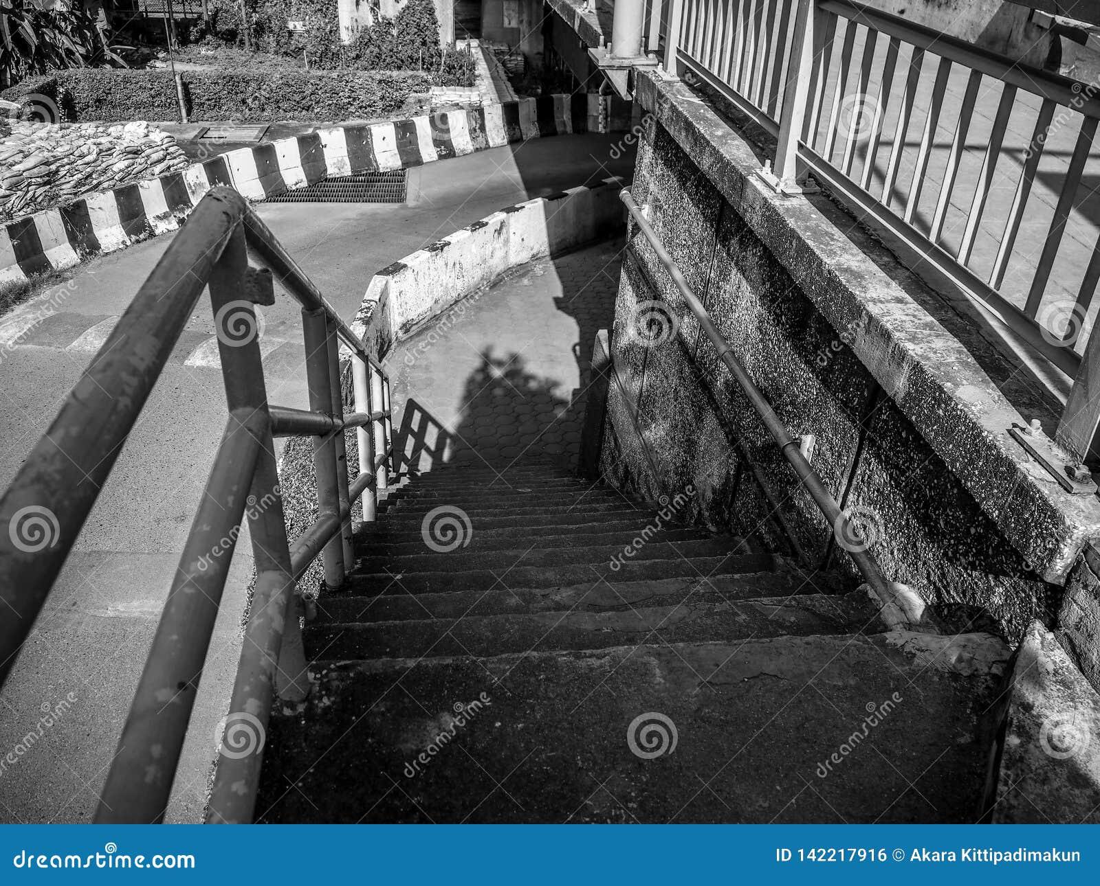 Конкретная лестница к вниз мосту, черно-белое фото