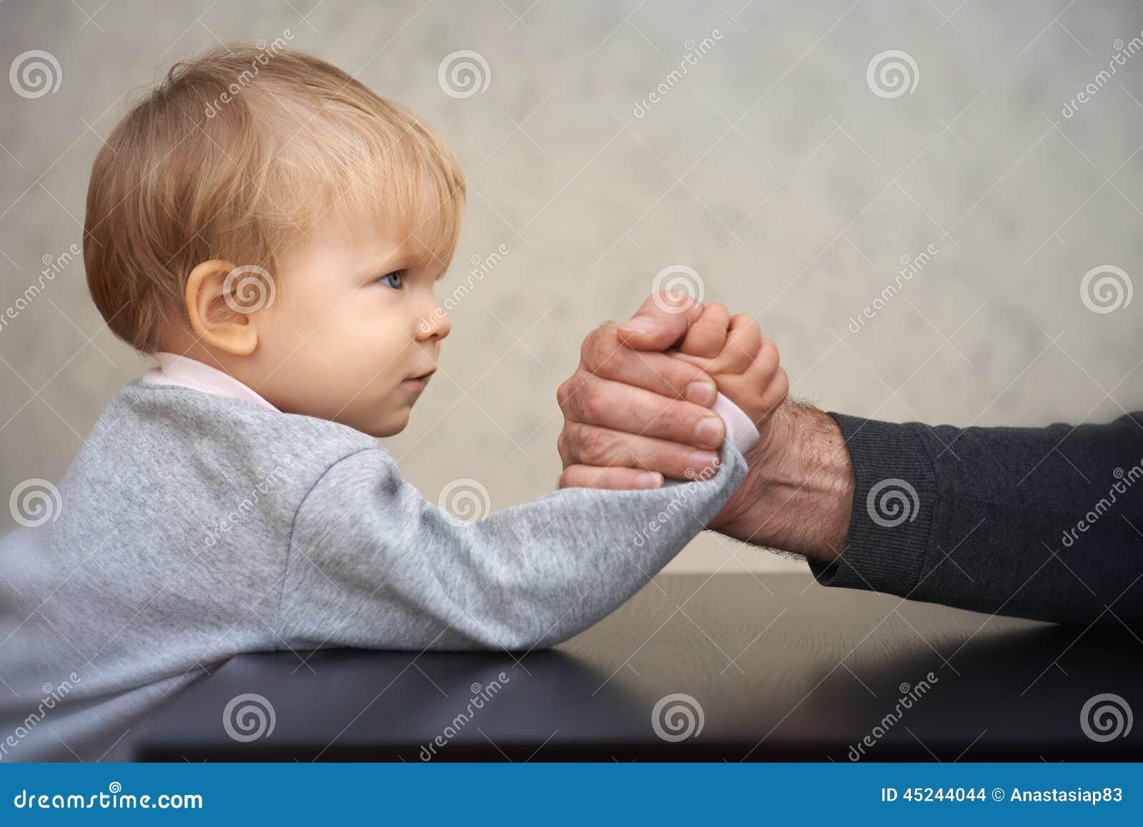 Конкуренция армрестлинга отца и ребенк