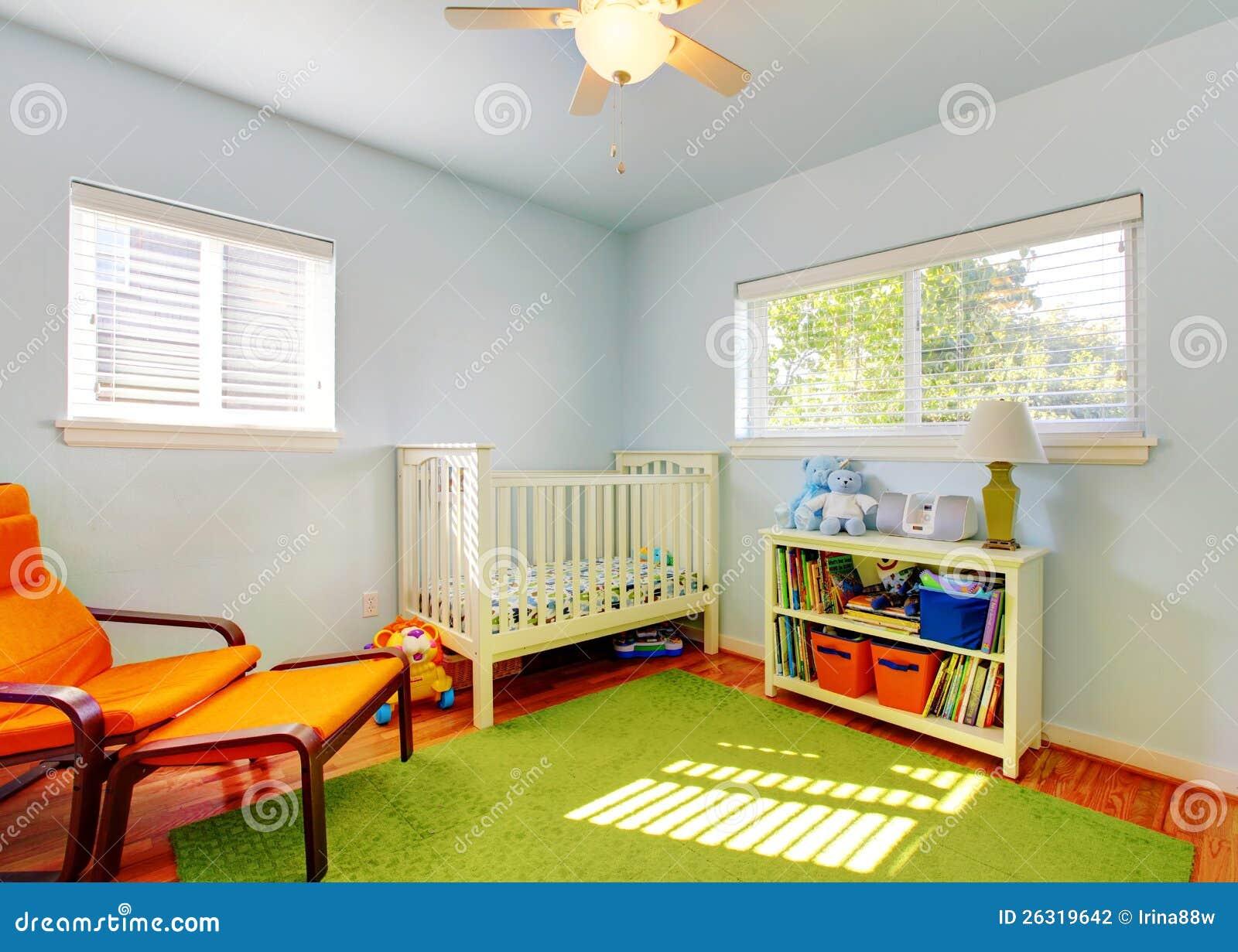 Конструкция комнаты питомника младенца с зеленым половиком, голубыми стенами и померанцовым стулом.