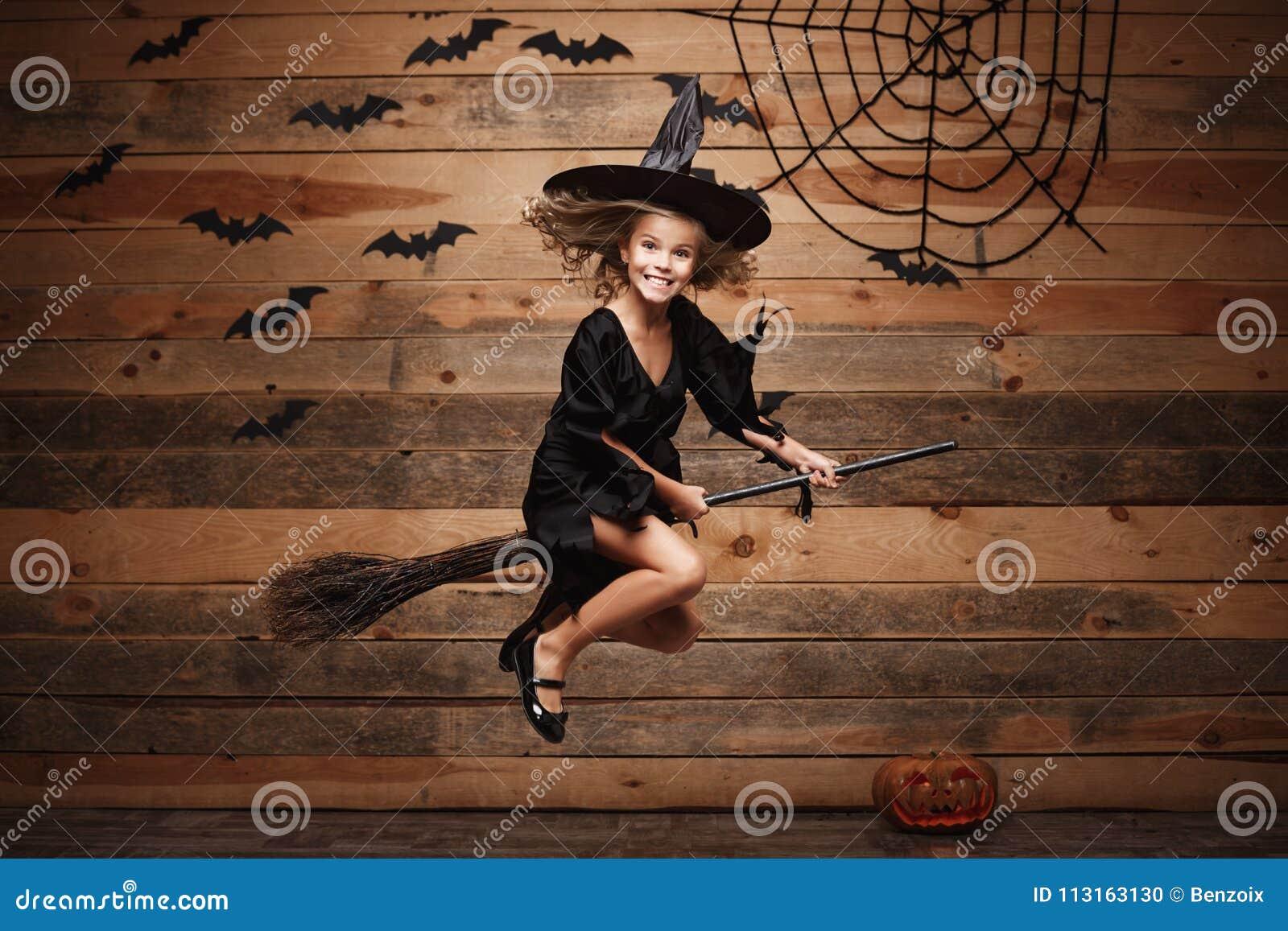 Концепция ведьмы хеллоуина - маленькое кавказское летание ребенка ведьмы на волшебном broomstick над предпосылкой летучей мыши и