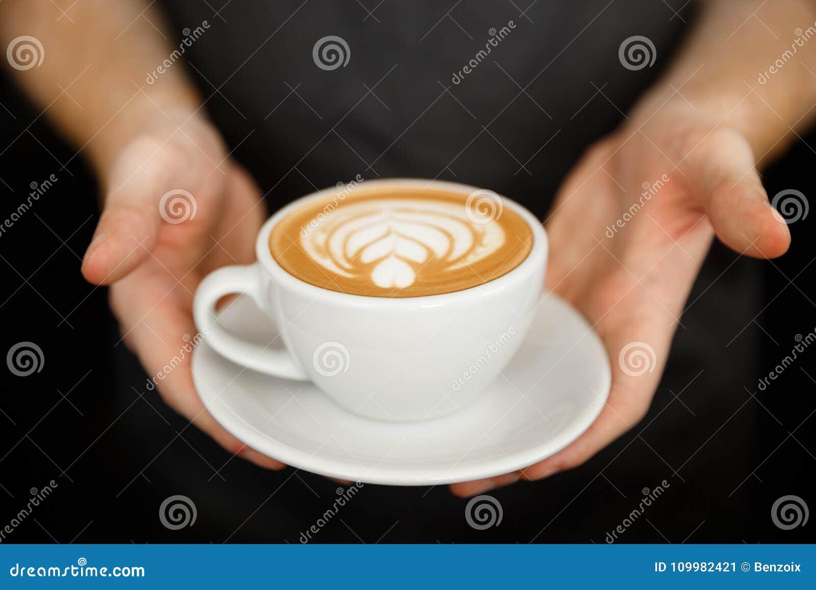 Концепция дела кофе - подрезанная близко вверх женского кофе сервировки с искусством latte пока стоящ в кофейне фокус