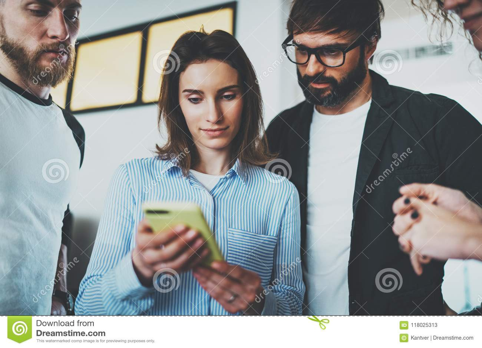 Концепция деловой встречи сотрудников Молодые женщины держа передвижную руку smartphone и показывая информацию к ее коллегам