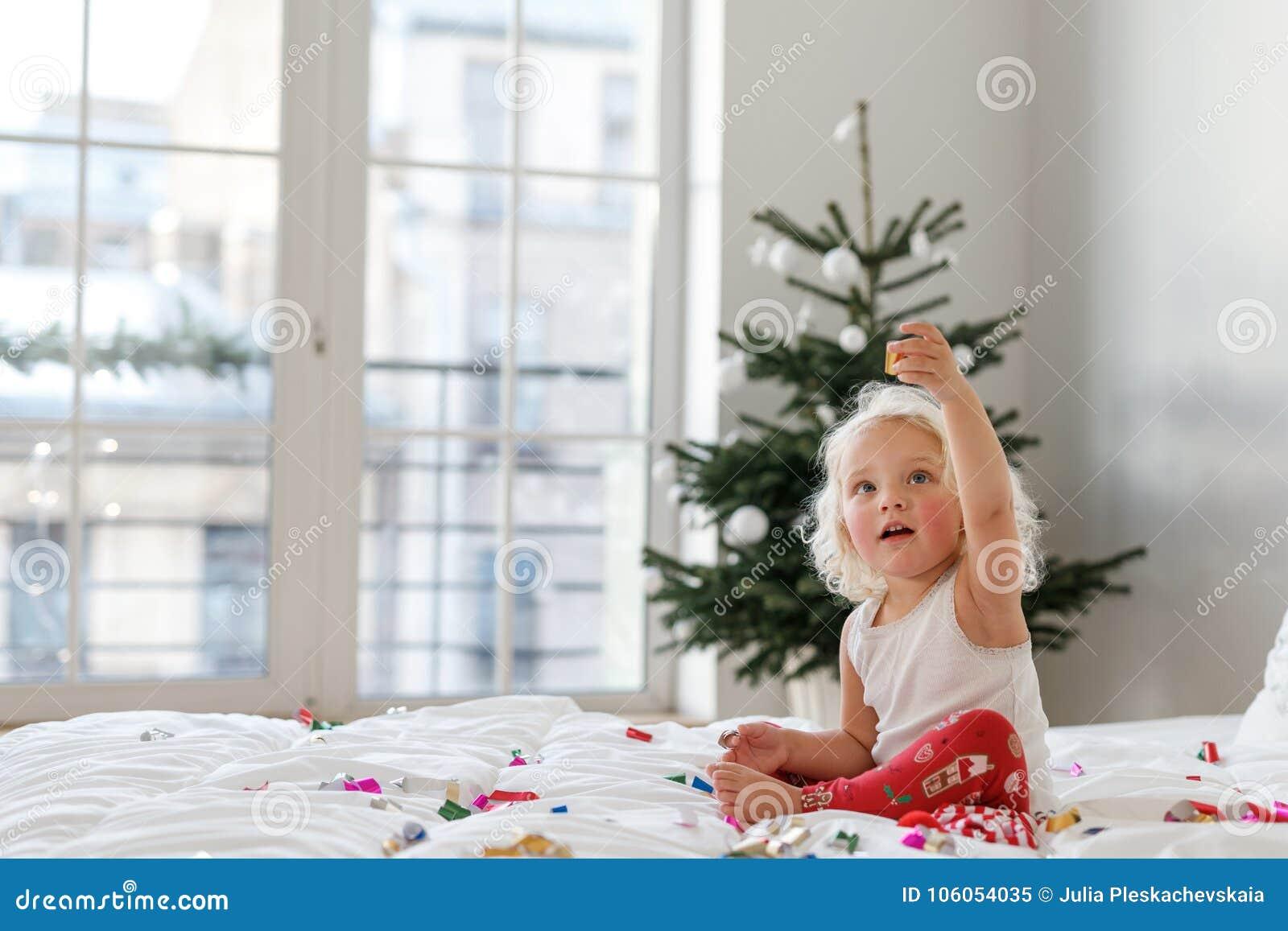 Концепция детей, рождества и Нового Года Прелестная белокурая девочка носит pyjamas, игры с красочным confetti дальше