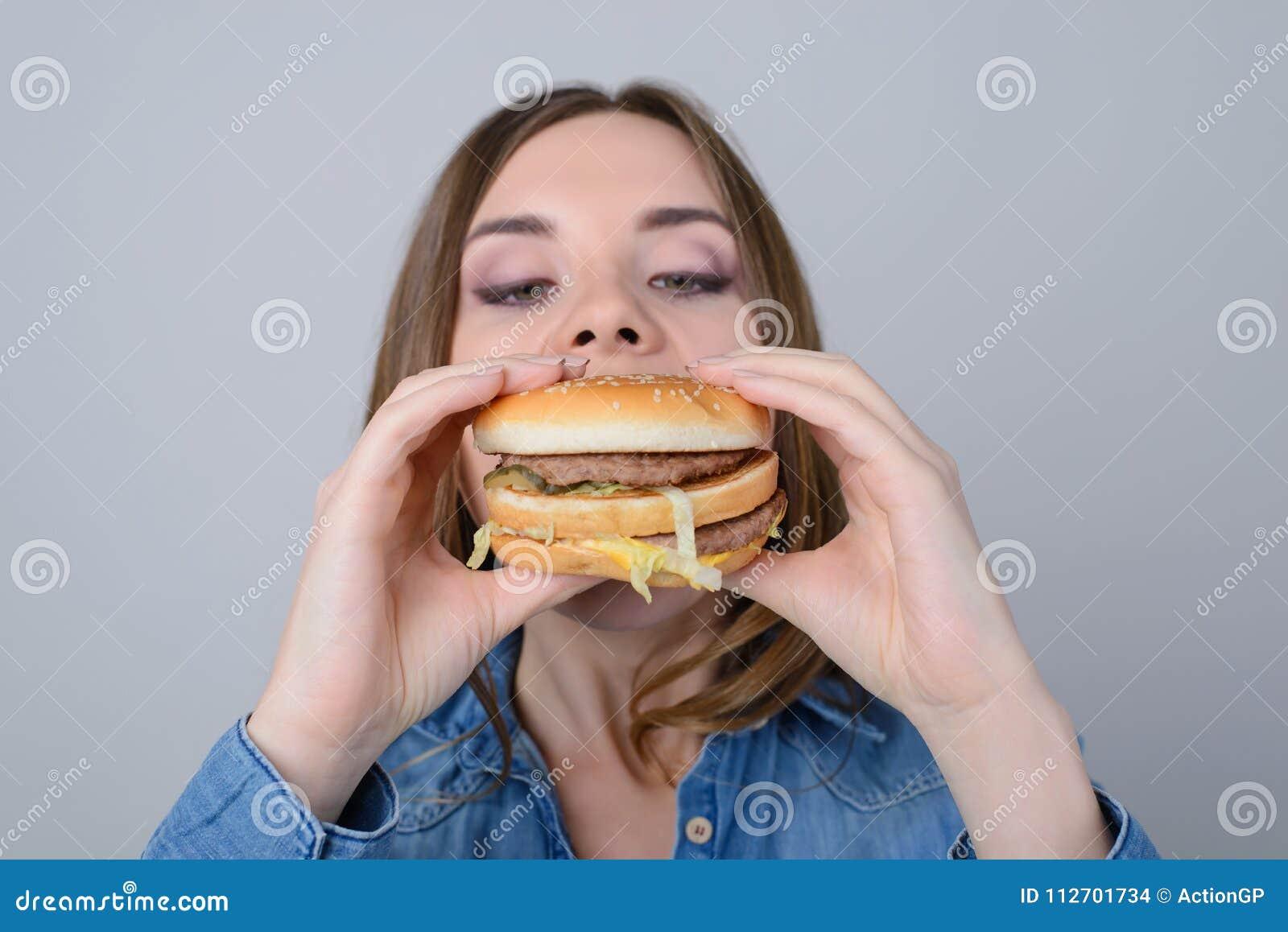 Концепция еды нездоровых закусок Голодная женщина сдерживая большой вкус
