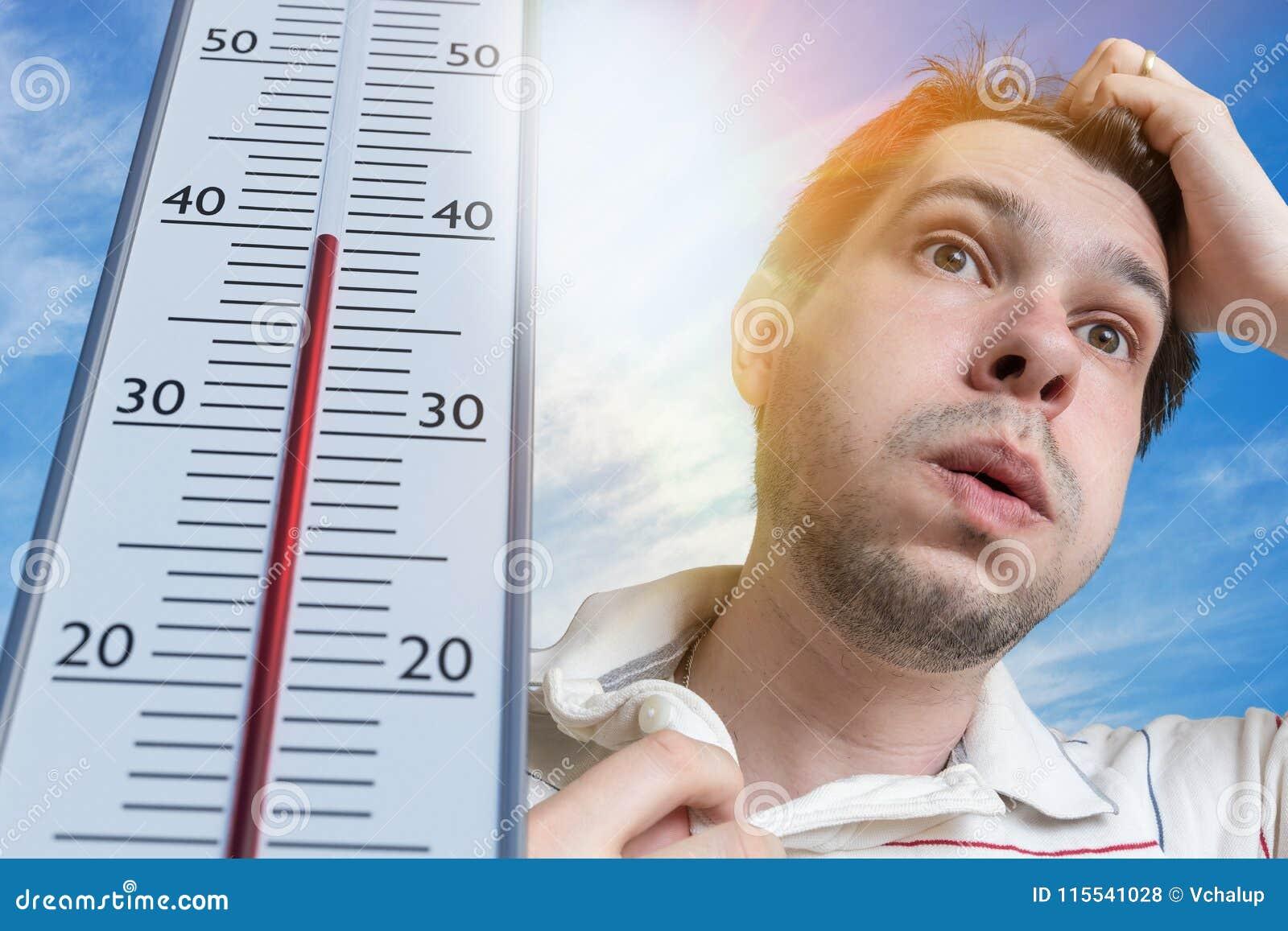 Концепция жаркой погоды Молодой человек потеет Термометр показывает высокую температуру Солнце в предпосылке
