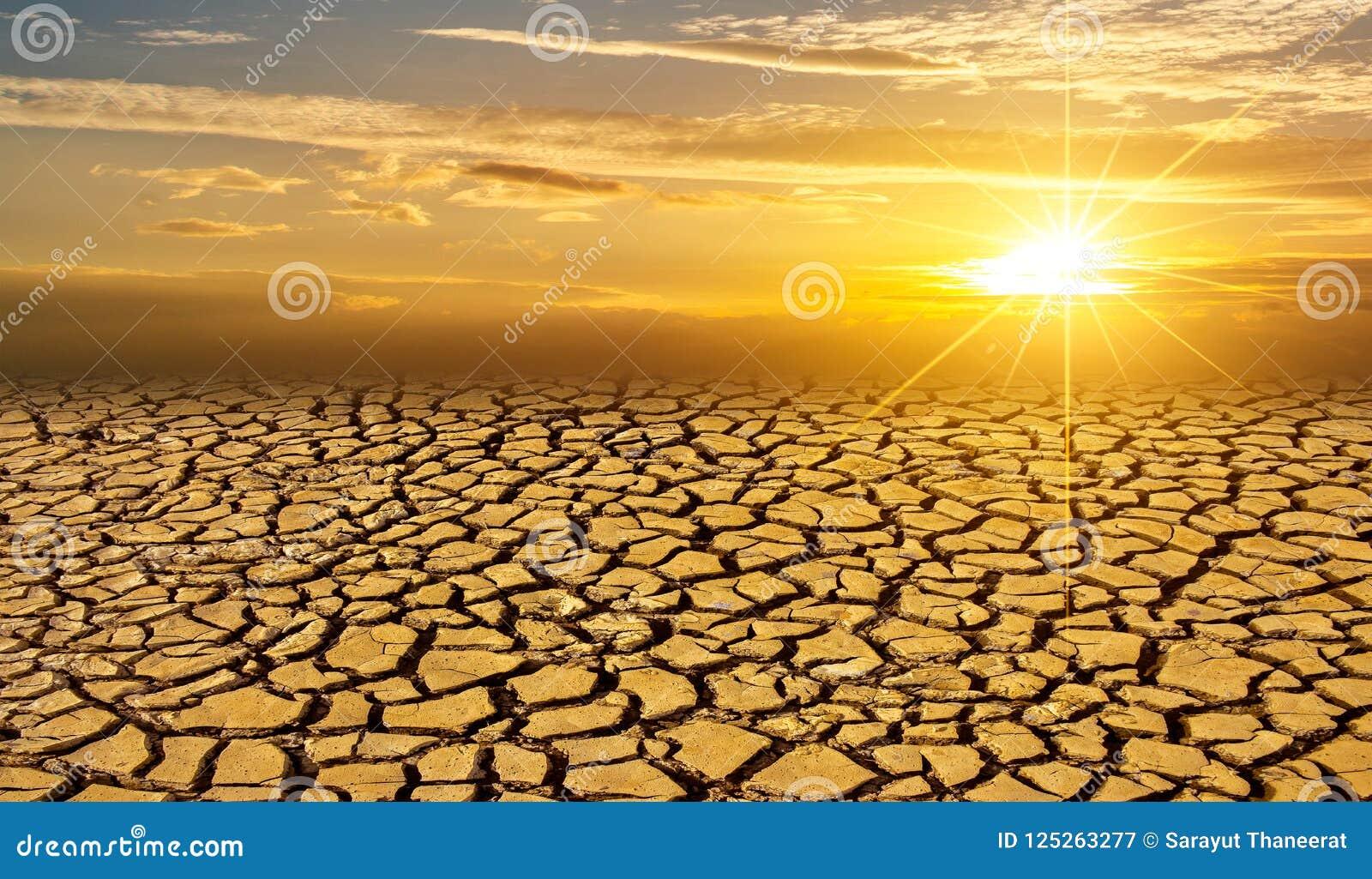Концепция засушливой пустыни Солнця почвы глины глобальная проникая треснула заход солнца ландшафта пустыни засухи почвы выжженно