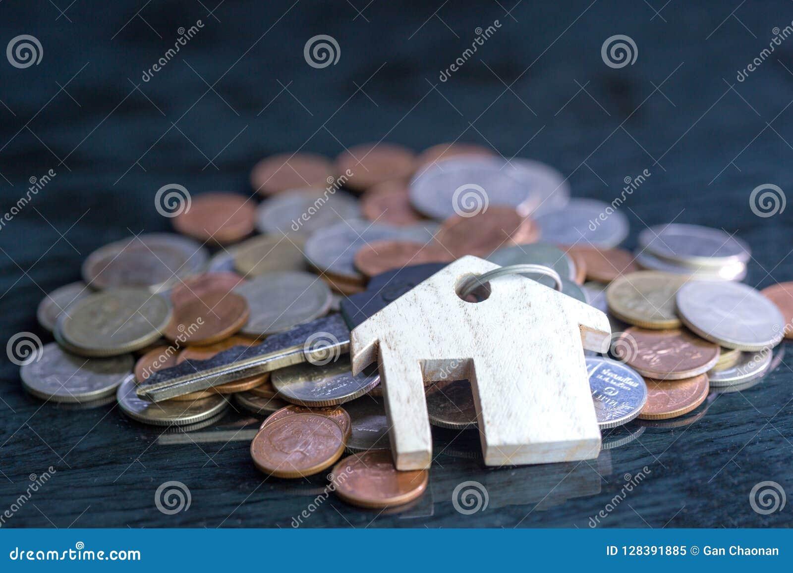 Концепция имущества, keychain с символом дома, ключи помещена на черной монетке предпосылки
