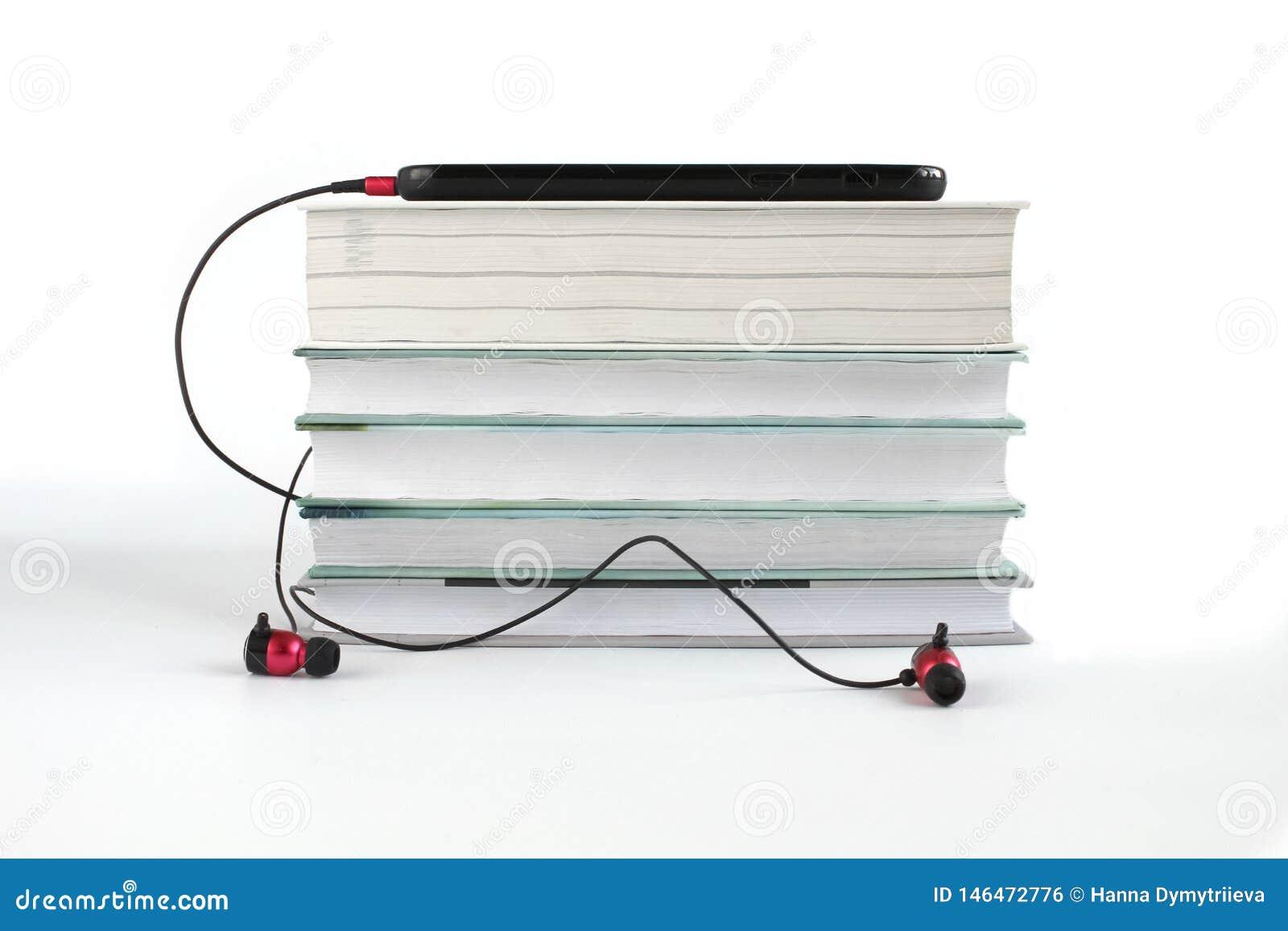 Концепция, который нужно слушать аудио книги Красные наушники около стога книг Белая предпосылка с космосом экземпляра для текста