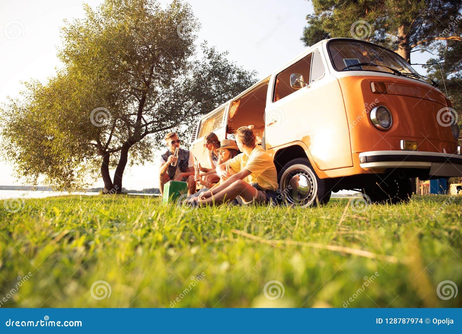 Концепция летних отпусков, поездки, каникул, перемещения и людей - усмехаясь молодые друзья hippie имея потеху над минифургоном