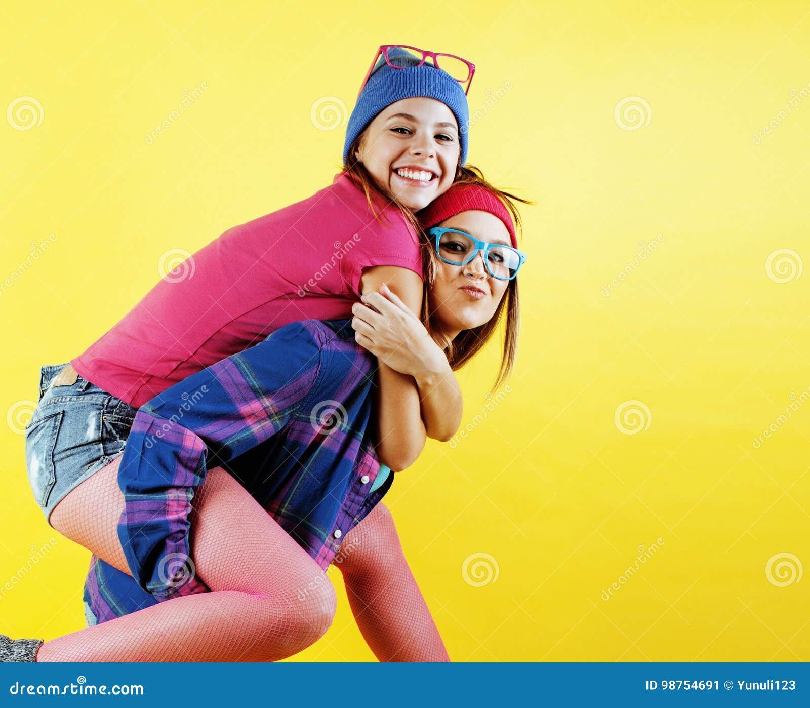 Концепция людей образа жизни: 2 довольно молодых девочка-подростка школы имея усмехаться потехи счастливый на желтой предпосылке