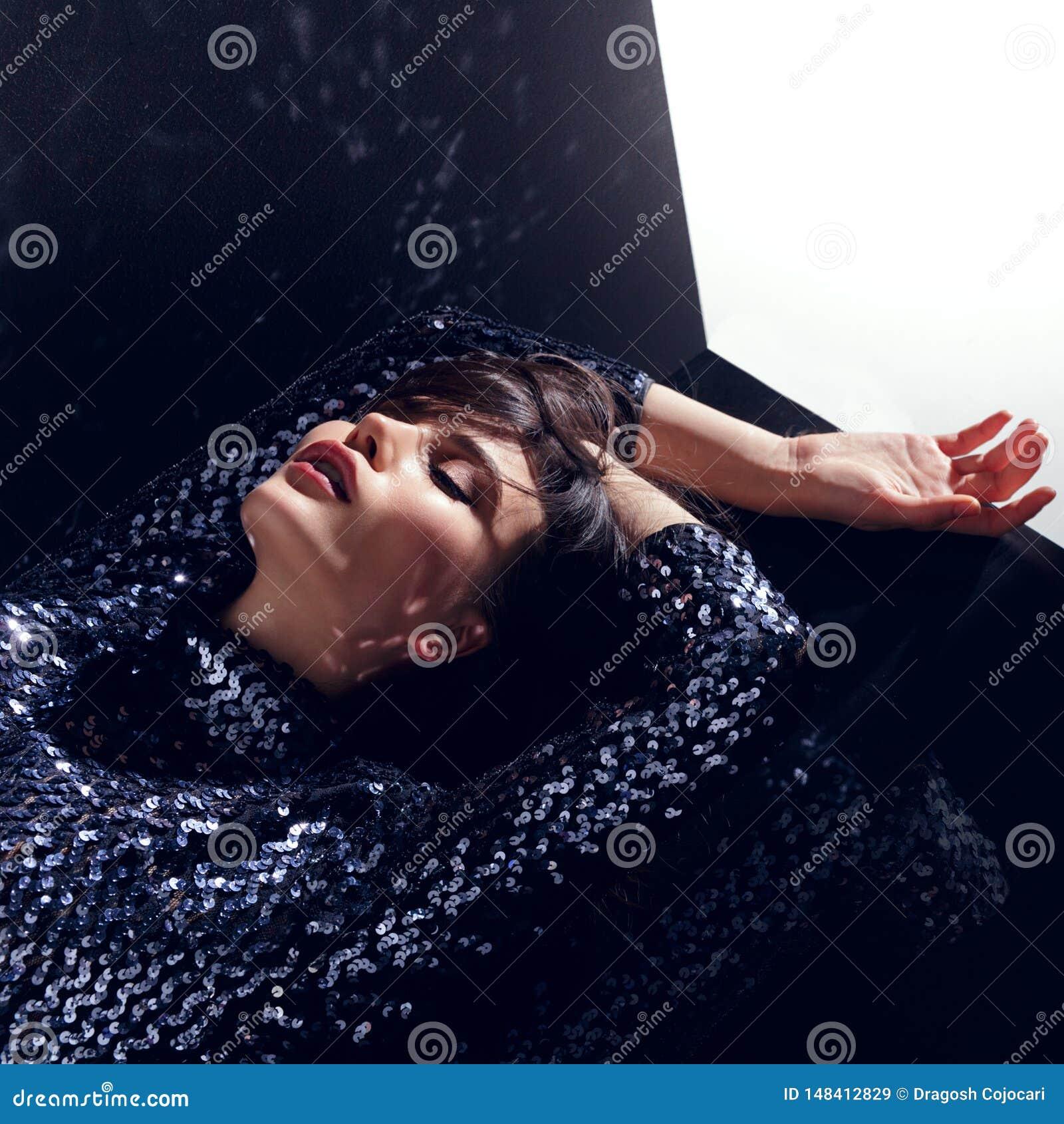 Концепция моды, шикарная модель, с закрытыми глазами в sequins одевает представлять в студии, изолированной на черной предпосылке