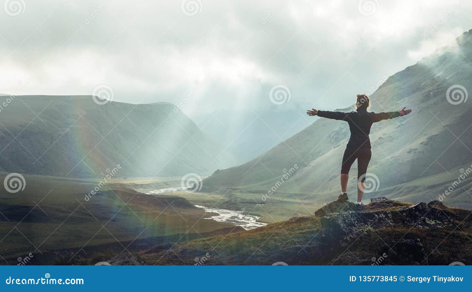 Концепция назначения перемещения открытия Молодая женщина Hiker с подъемами рюкзака к верхней части горы против фона захода солнц