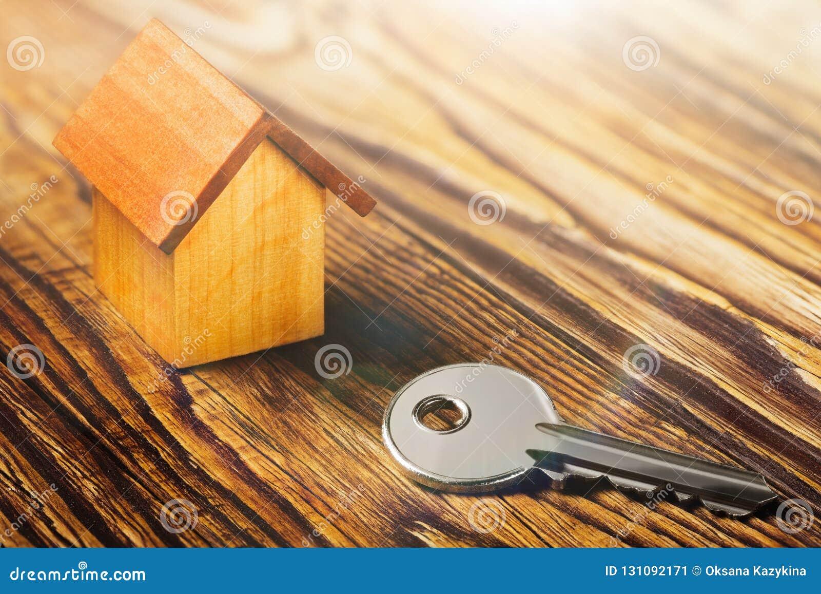 Концепция недвижимости с домом и ключ на деревянной предпосылке Концепция имущества идеи по-настоящему, личное свойство a