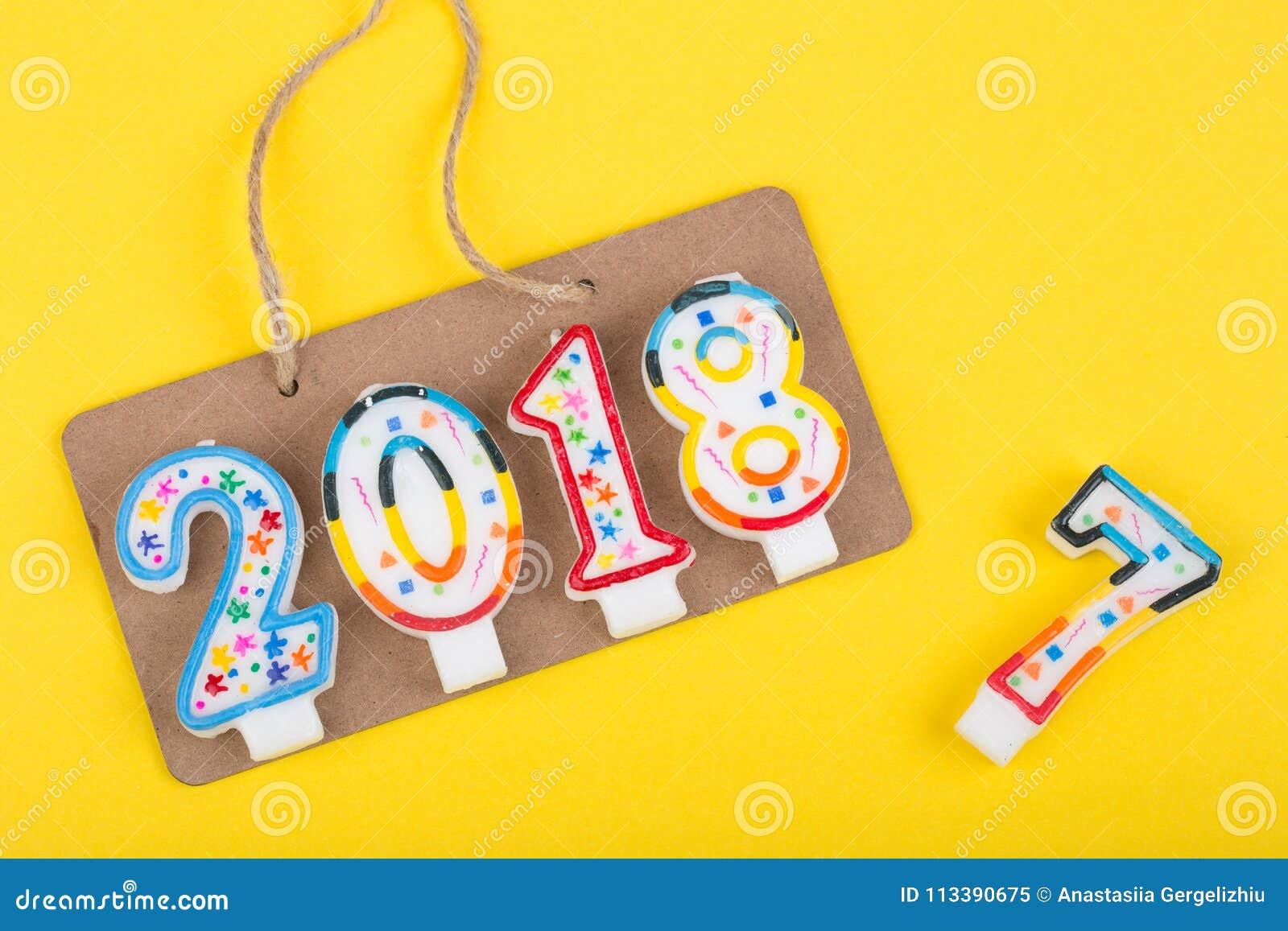Концепция Нового Года - знак на веревочке с надписью 2018 делает из свечей и до свидания 2017 год