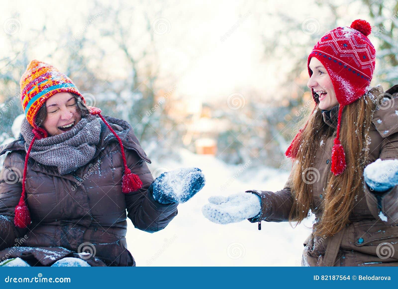 Концепция образа жизни зимы - девушки имея потеху в парке