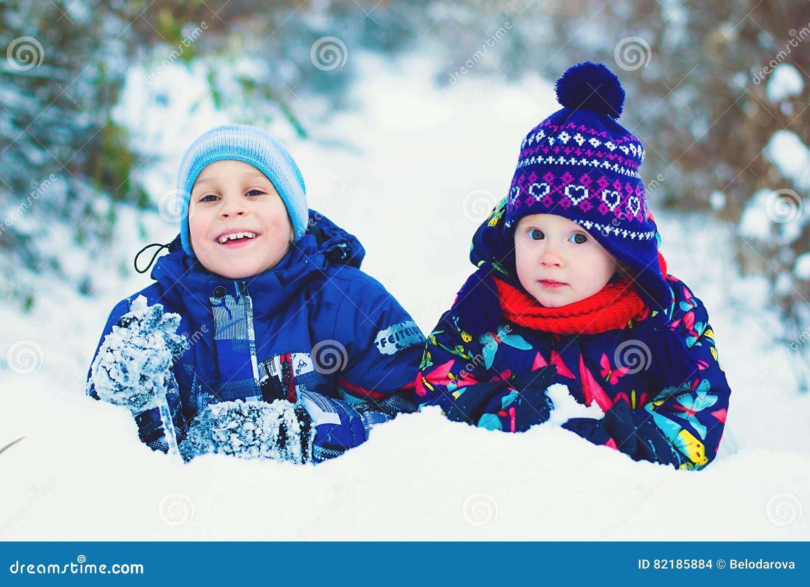 Концепция образа жизни зимы - дети имея потеху в парке