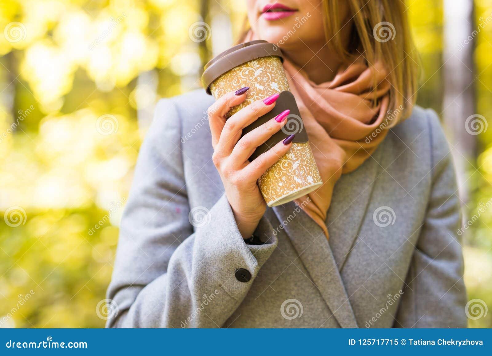 Концепция осени, питья и кофе - близкая вверх женщины в сером пальто с чашкой кофе