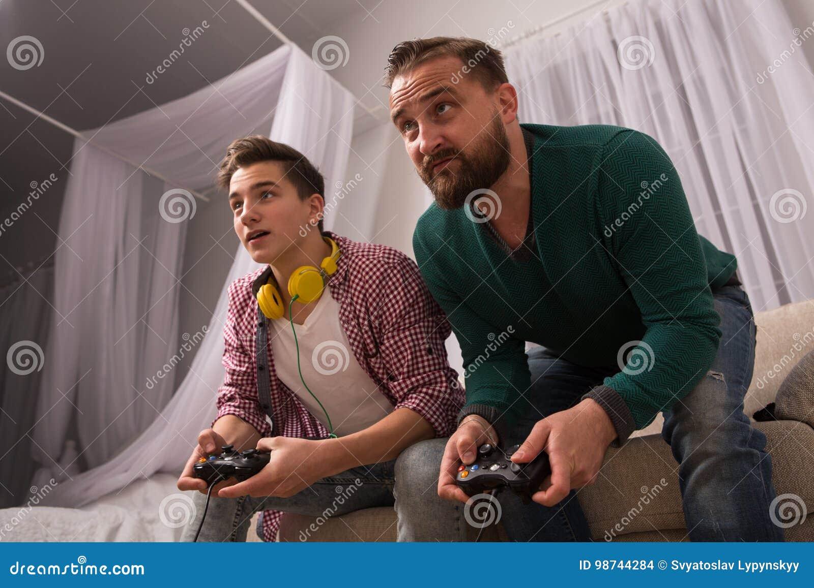 Концепция, отец и сын видеоигры наслаждаясь играющ консоль совместно