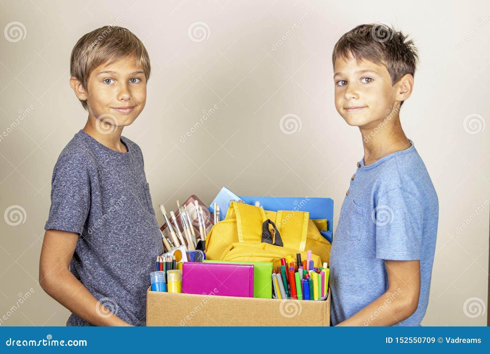 Концепция пожертвования Удержание детей дарит коробку с книгами и школьными принадлежностями