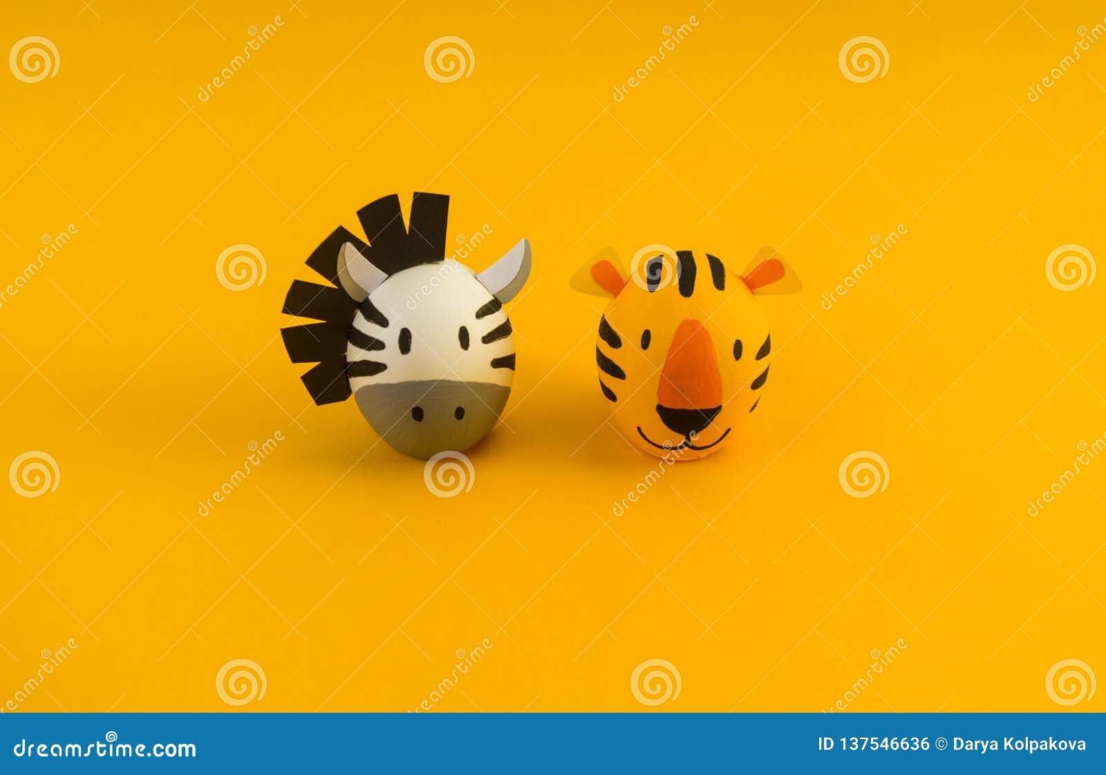 Концепция праздника пасхи с милыми handmade яйцами: оранжевые тигр и зебра