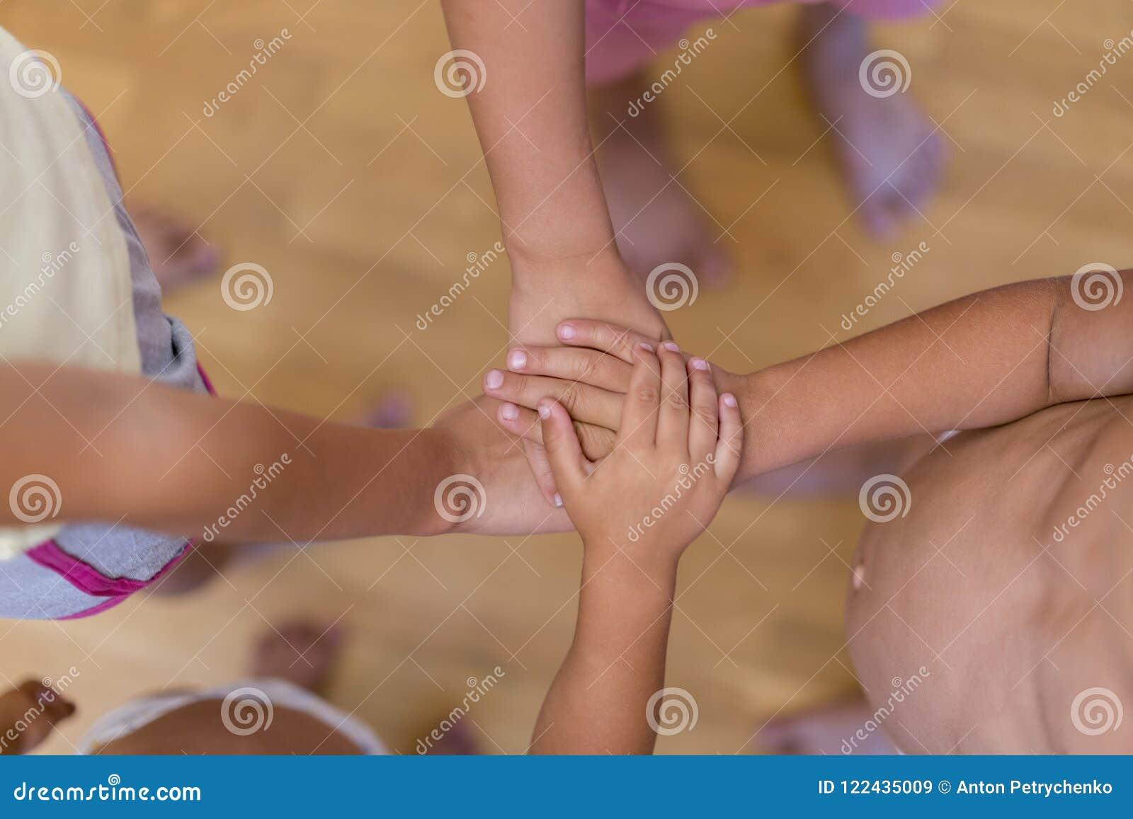 Концепция приятельства и взаимопомощи ребенка Руки детей штабелированные к единству Штабелированные руки детей