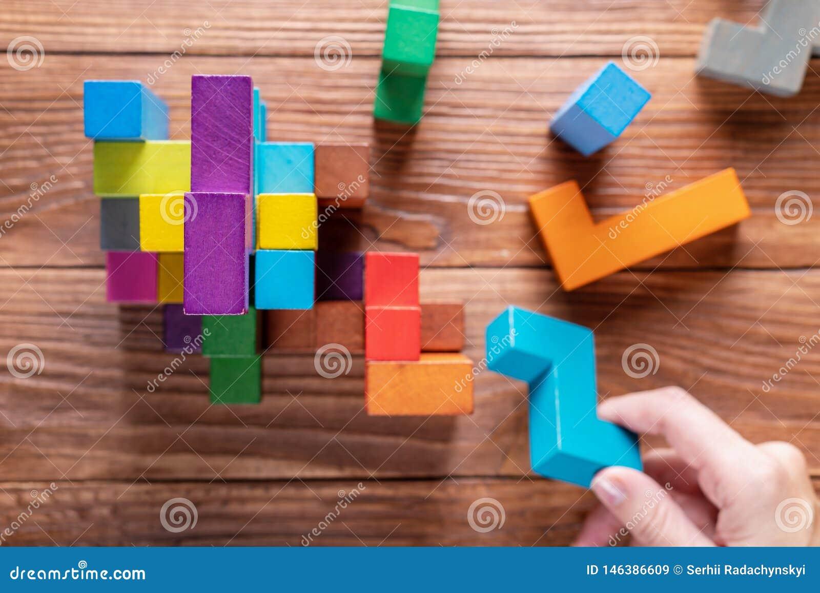 Концепция процесса принятия решения, логического мышления Рука держа деревянный элемент головоломки
